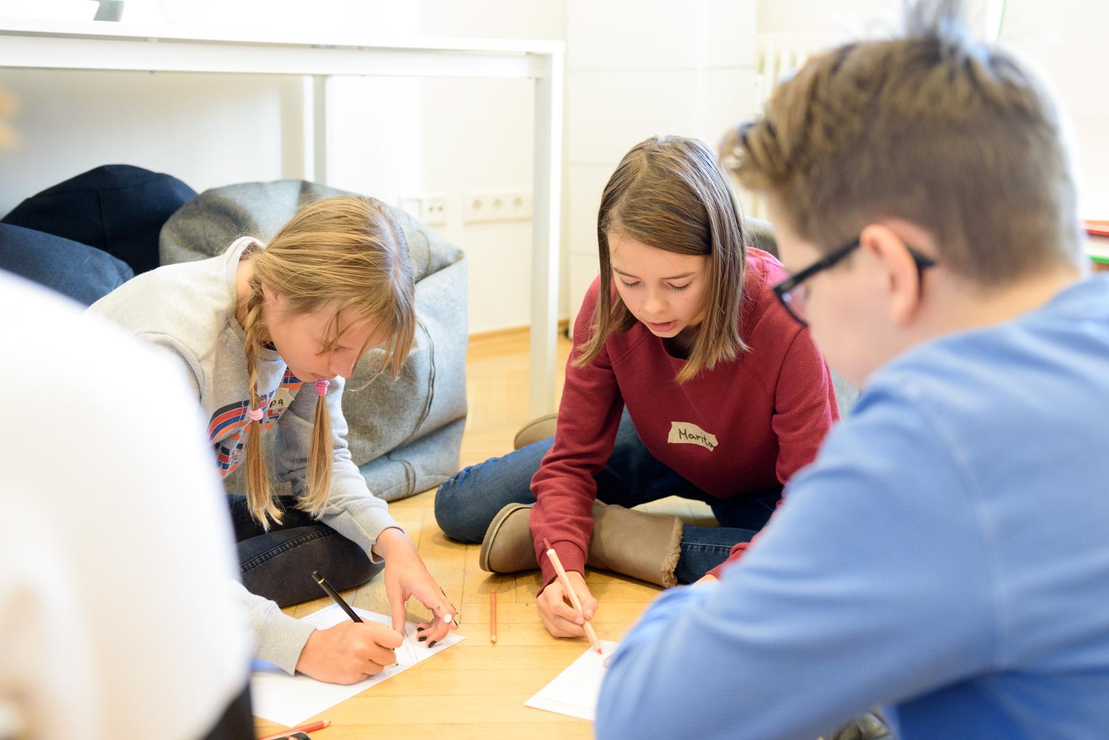 Zwei Mädchen, ein Junge und eine weitere Person sitzen im Kreis auf dem Boden. Vor ihnen liegen Zettel und sie malen mit Buntstiften auf die Zettel.