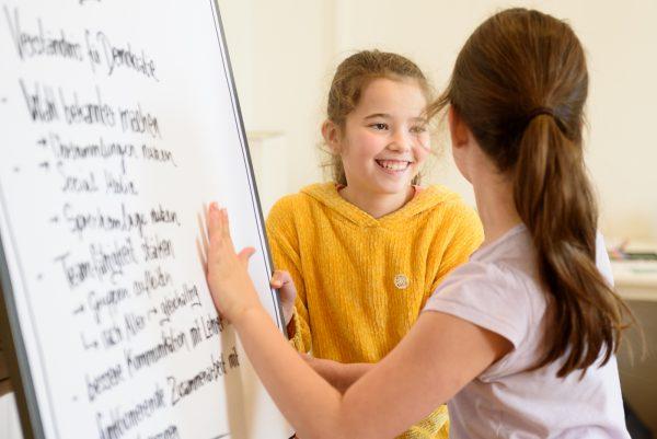 Zwei Mädchen stehen vor einem Flipchart und lächeln sich an.