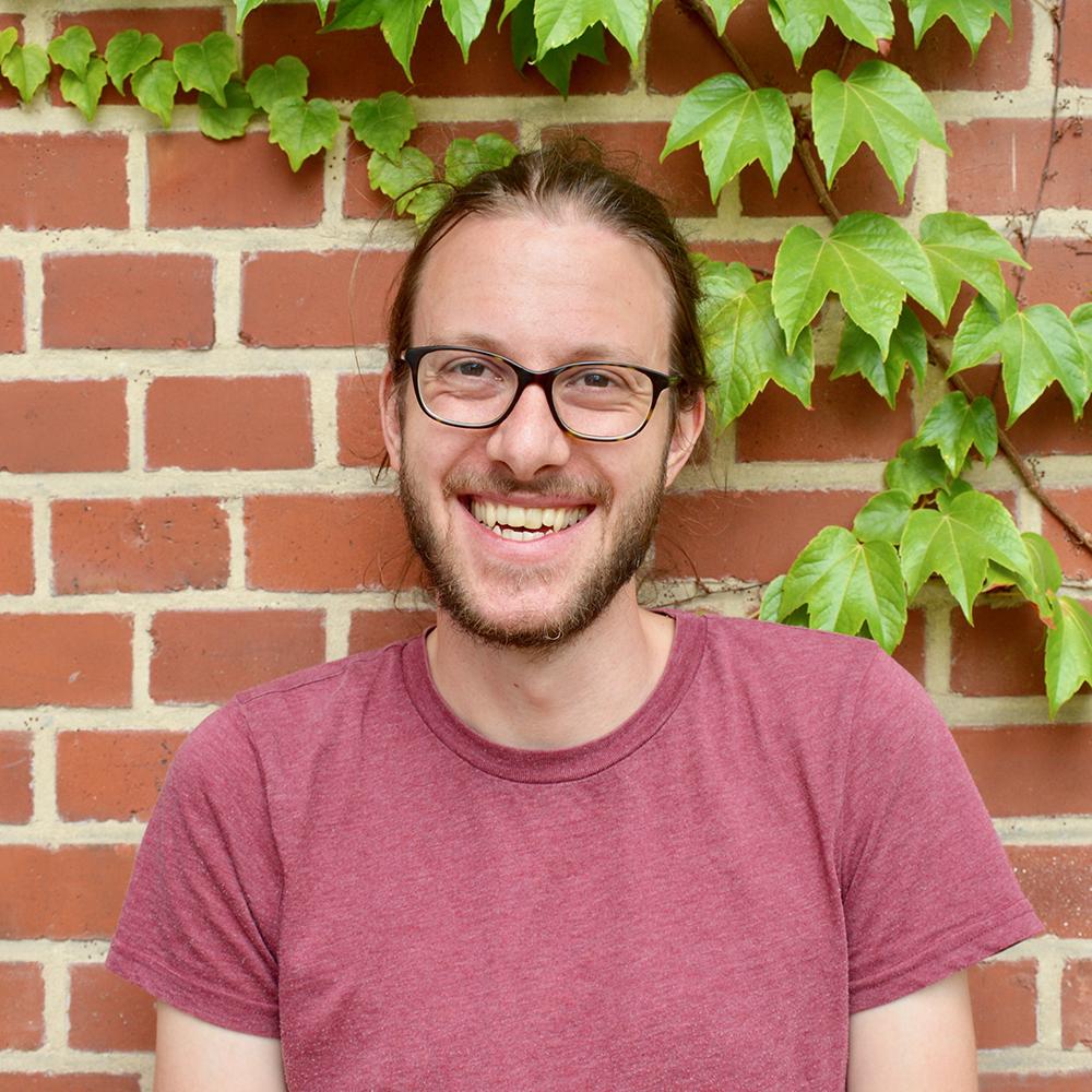 Das Bild zeigt Gunnar von der Servicestelle Jugendbeteiligung. Er steht vor einer mit Efeu bewachsenen Backsteinwand und lacht in die Kamera. © Servicestelle Jugendbeteiligung e.V., 2020