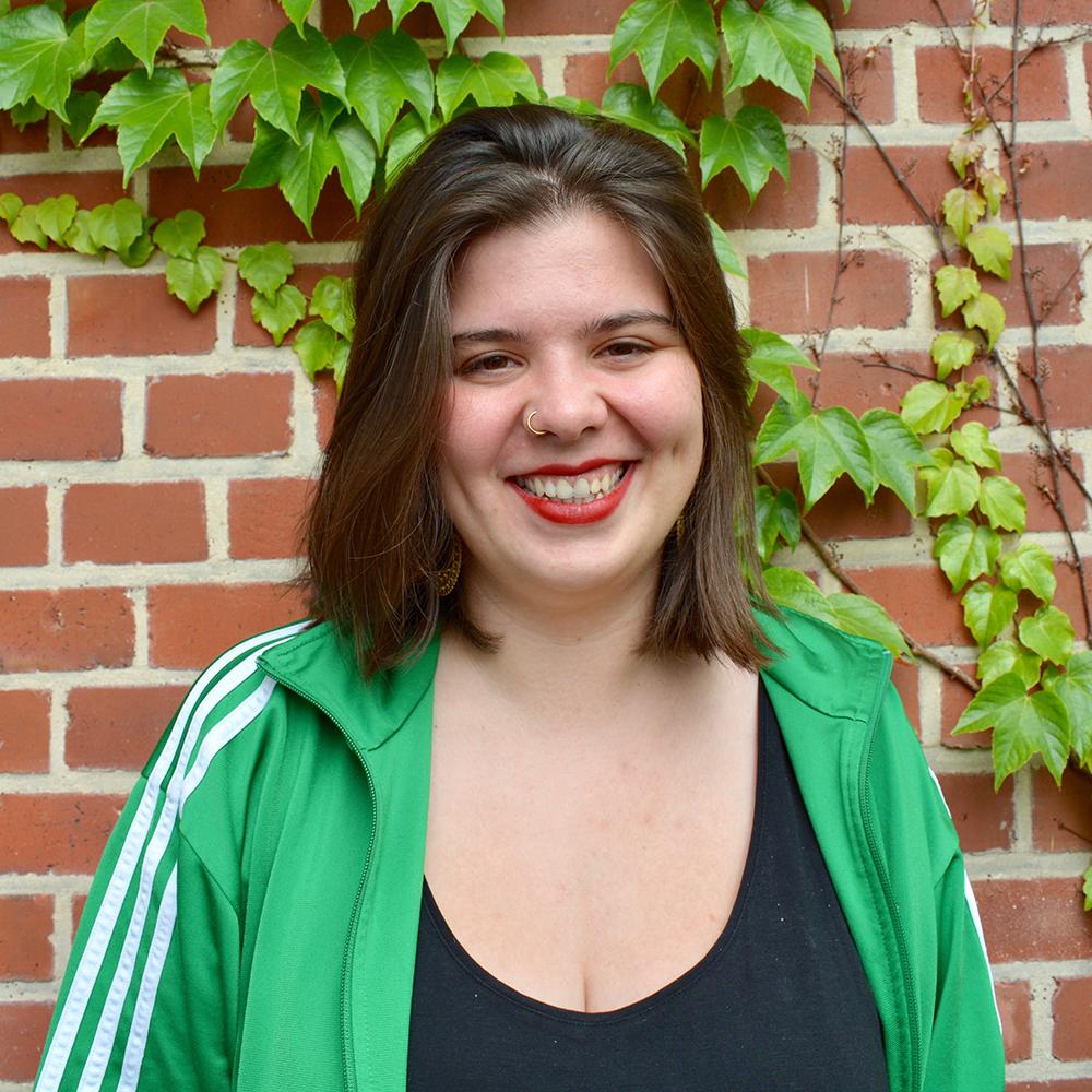 Das Bild zeigt Nina von der Servicestelle Jugendbeteiligung. Sie steht vor einer mit Efeu bewachsenen Backsteinwand und lacht in die Kamera. © Servicestelle Jugendbeteiligung e.V., 2020