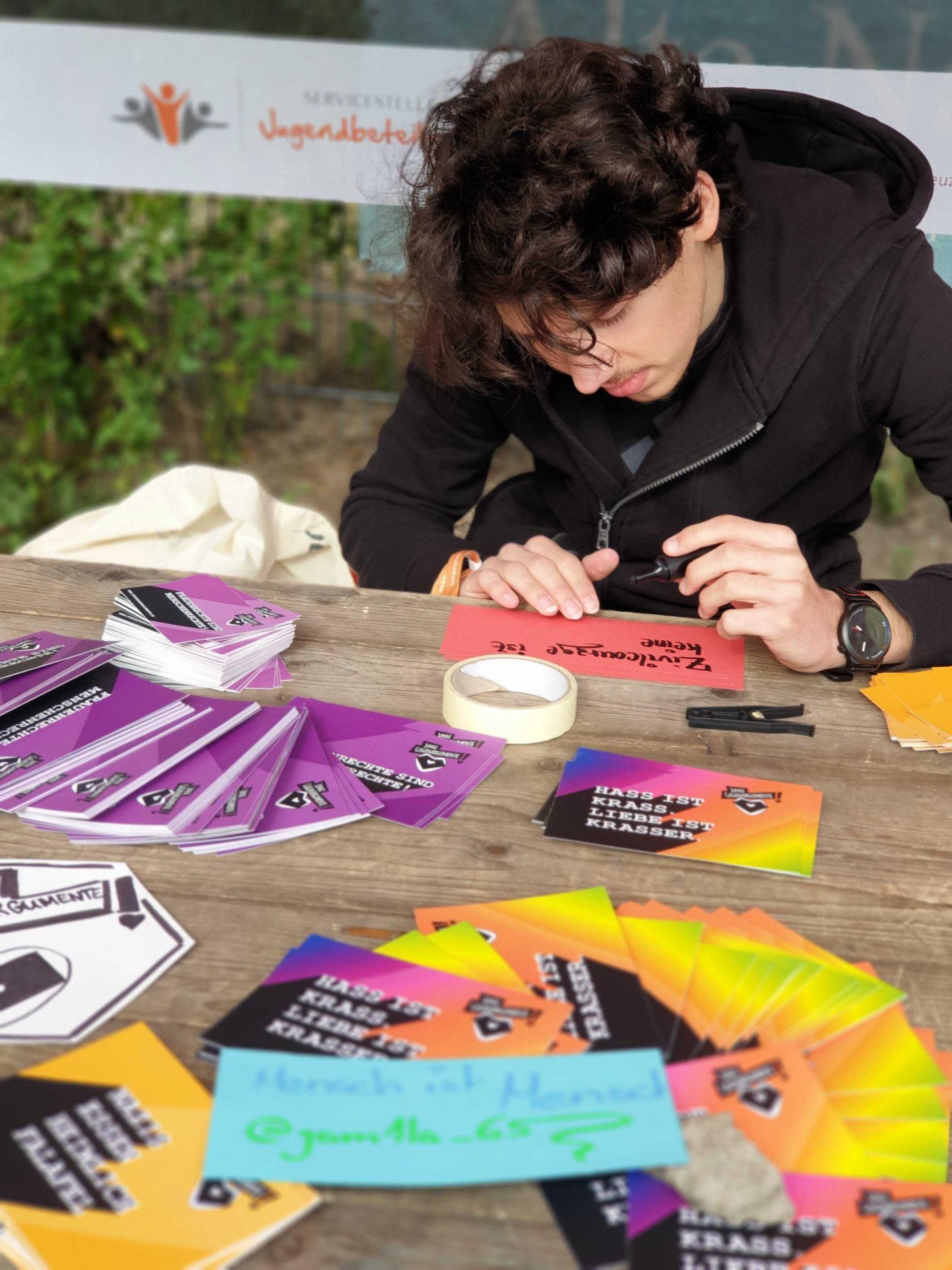 Eine Person sitzt an einem Tisch und schreibt auf eine Karte. Auf dem Tisch liegen viele Flyer und Postkarten. Auf dem Bild sieht man zwei Personen, die an einem Tisch sitzen und etwas aufschreiben. .© Servicestelle Jugendbeteiligung e.V., 2019
