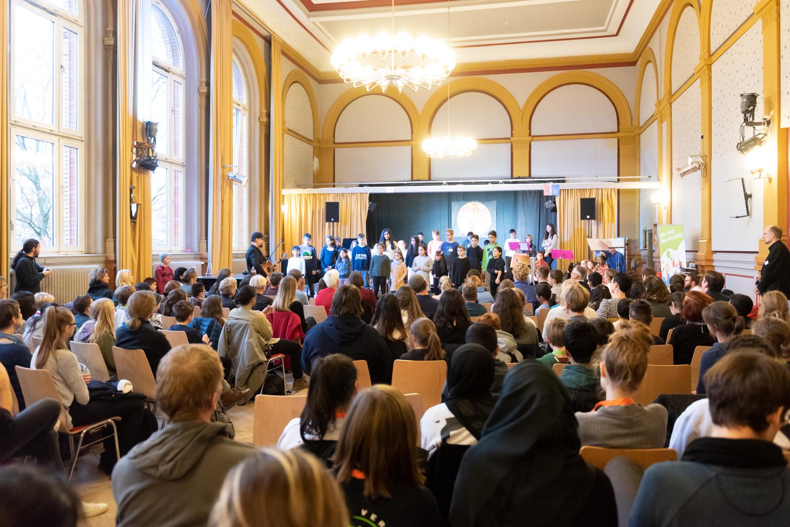 In einem Raum ist eine Bühne aufgebaut. Auf der Bühne steht eine Gruppe von Schüler*innen. Vor der Bühne sitzen viele Zuschauer im Plenum.