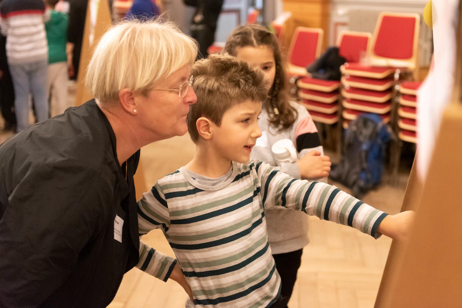 Zwei Kinder stehen mit ihrer Lehrerin vor einer Pinnwand und diskutieren über den Inhalt auf der Pinnwand. Ein Kind zeigt auf etwas. © Servicestelle Jugendbeteiligung e.V., 2020