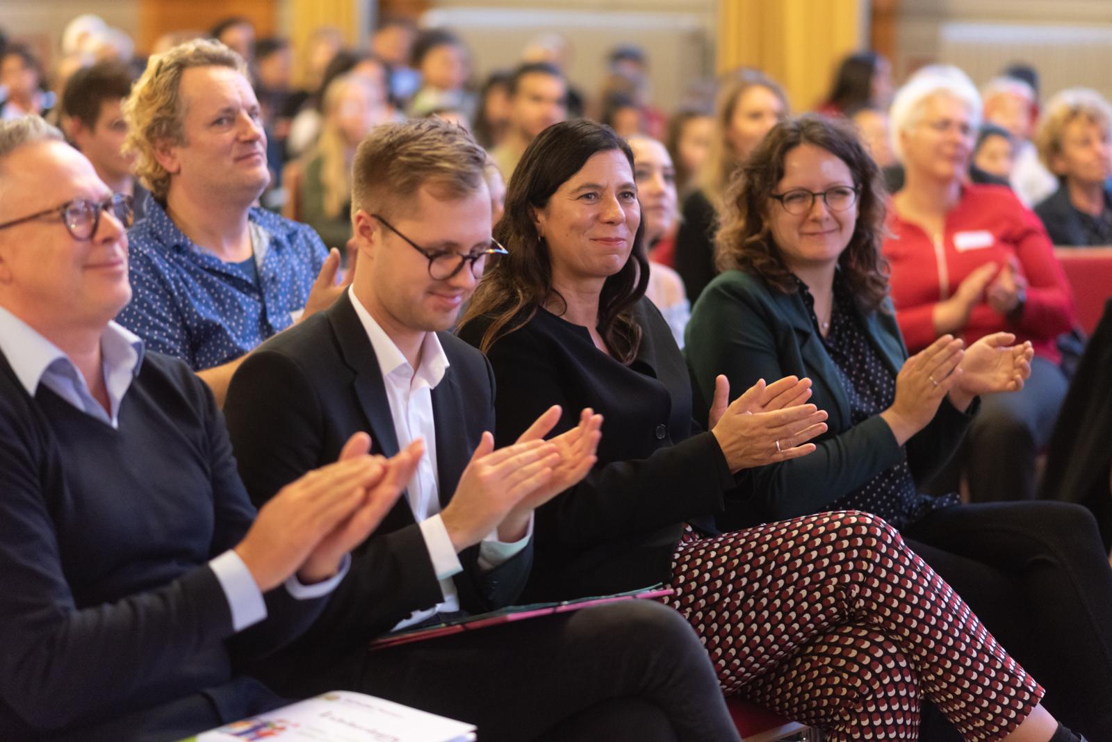 Viele Menschen sitzen im Plenum und applaudieren.
