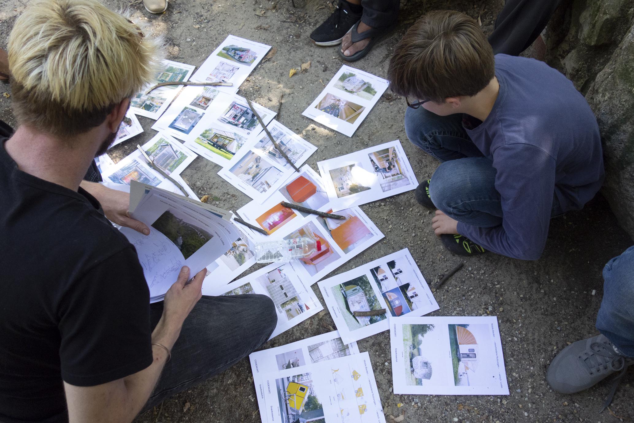 Ein junger Mann und ein Junge knien auf dem Fußboden. Vor ihnen sind mehrere Blätter mit Bildern ausgebreitet. Der Mann hält einige weitere Blätter mit Bildern in der Hand.