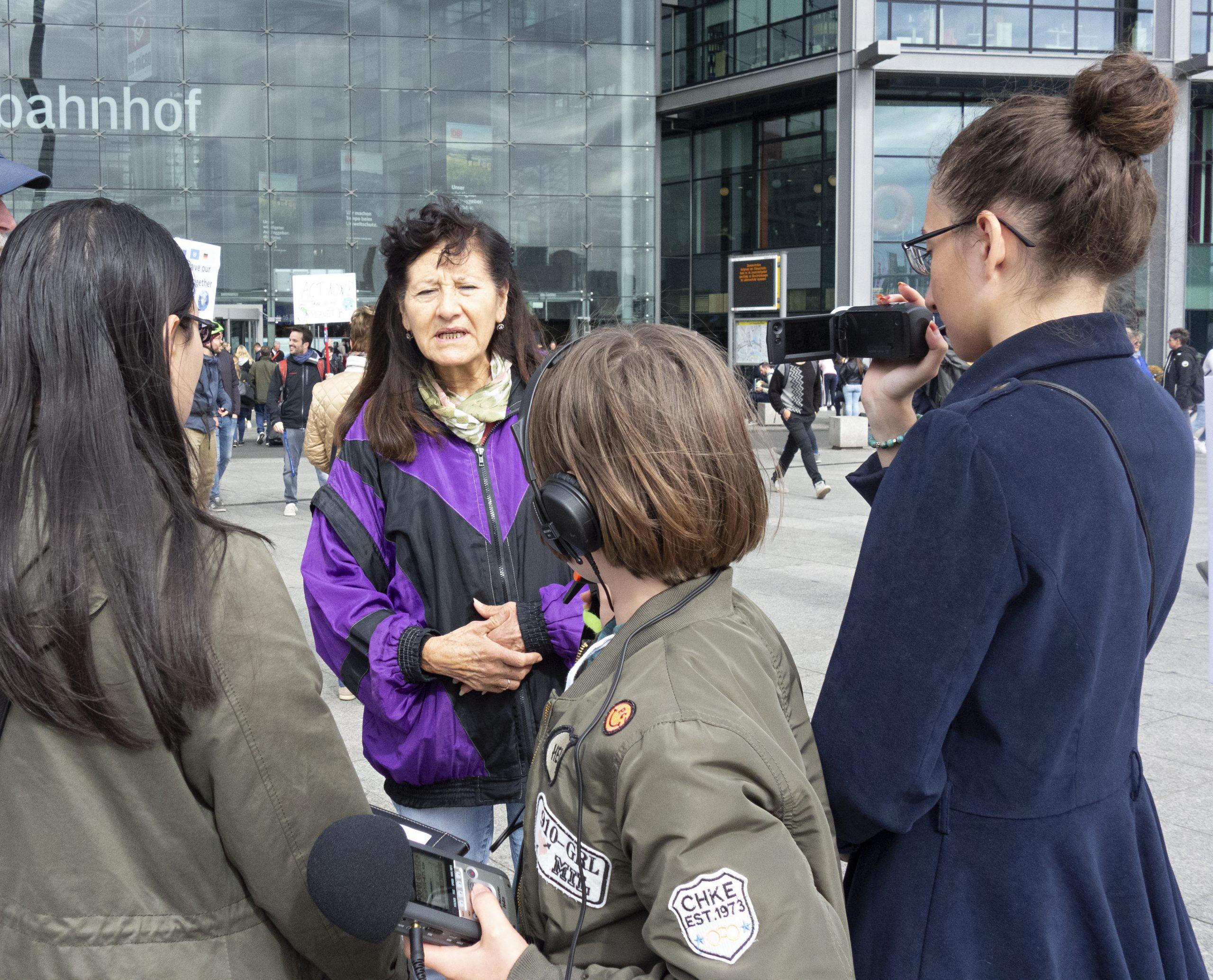 Drei junge Menschen mit Kamera und Mikrophone in der Hand interviewen eine Frau. Die Personen stehen vor dem Hauptbahnhof in Berlin.