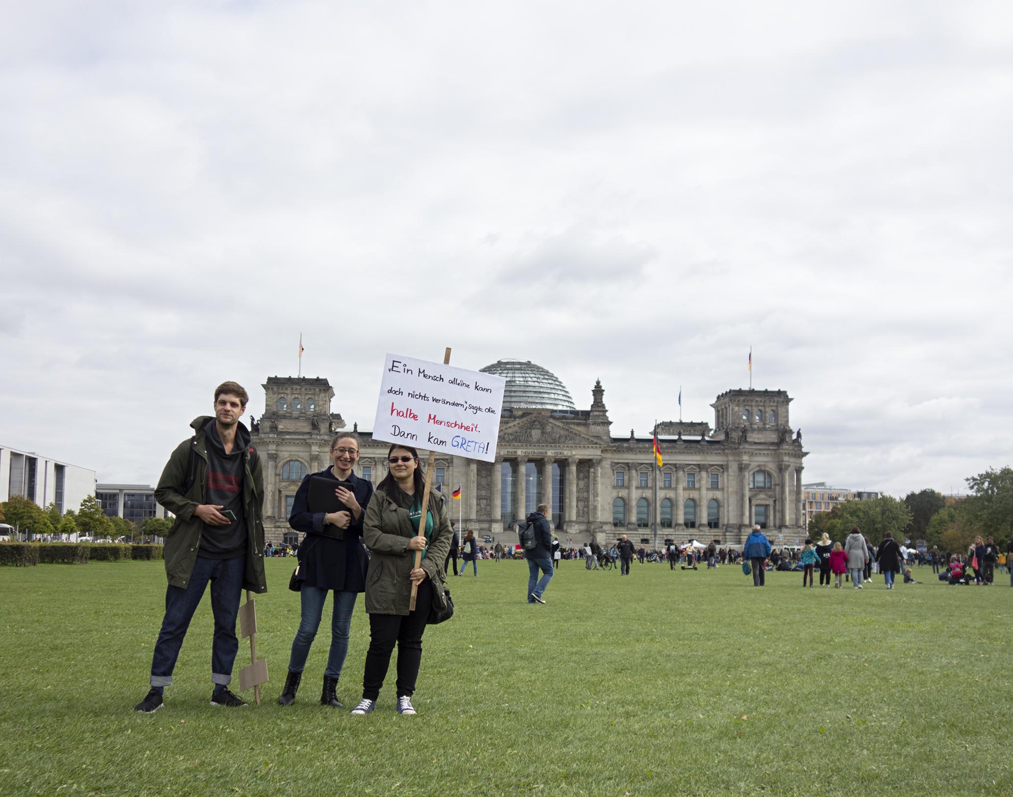 """Drei Personen stehen auf der Wiese vor dem Reichstagsgebäude. Eine der Personen hat ein Schild in der Hand. Auf dem Schild steht: """"Ein Mensch alleine kann doch nichts verändern. sagte die halbe Menschheit. Dann kam Greta."""""""