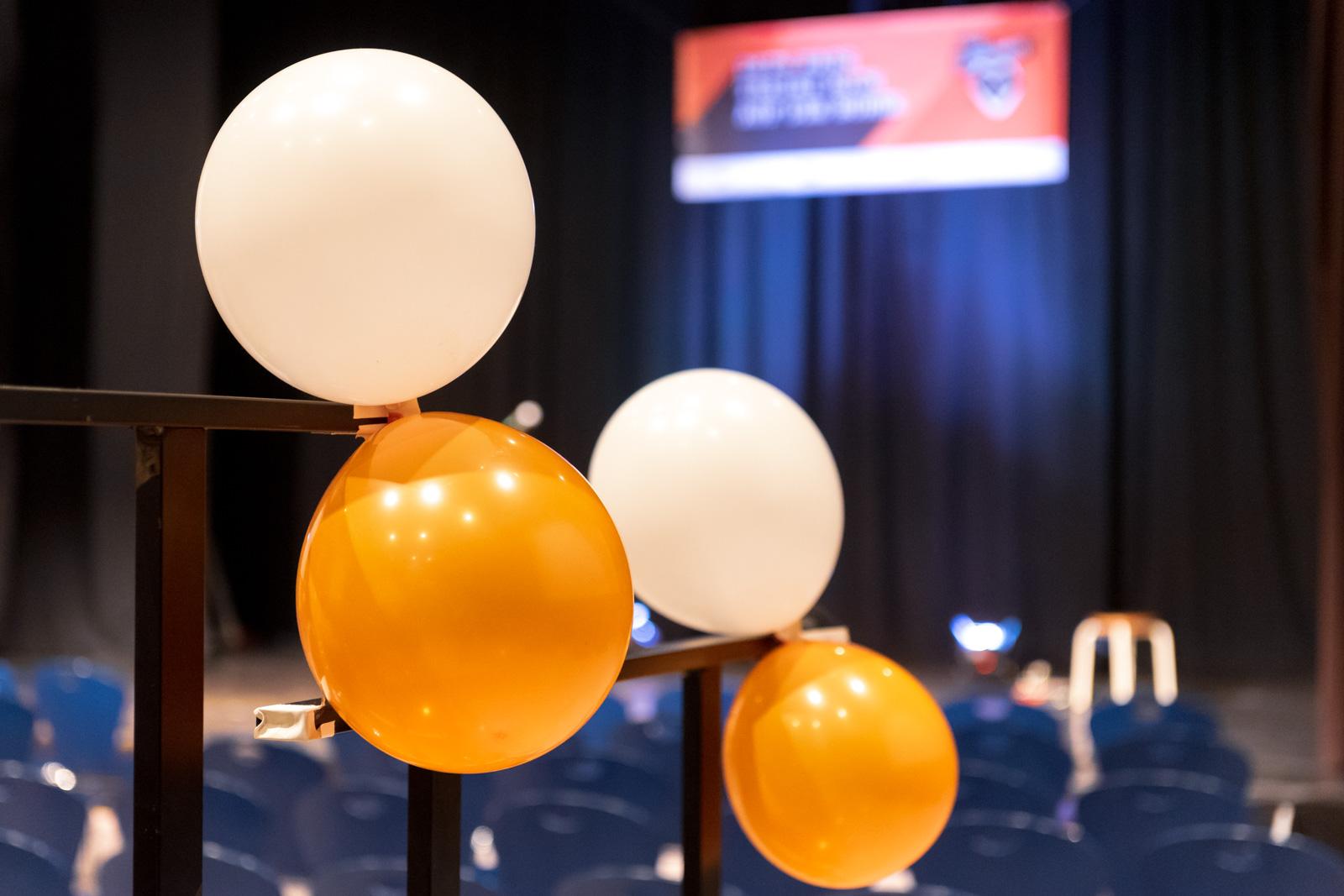 In einer großen Aula ist vorne eine Bühne und davor wurden Stühle aufgebaut. Im Fokus sind vier Luftballons zu sehen. Jeweils zwei der Ballons, ein weißer und ein orangener hängen zusammen an einem Geländer.