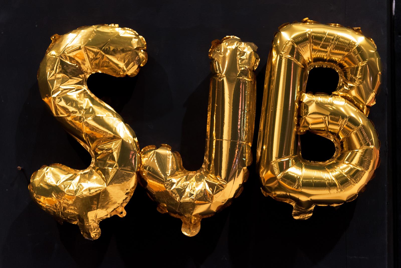 """Drei goldene Folienballons sind vor einem schwarzen Hintergrund. Die Folienballons sind Buchstaben und stellen das Wort """"SJB"""" da."""