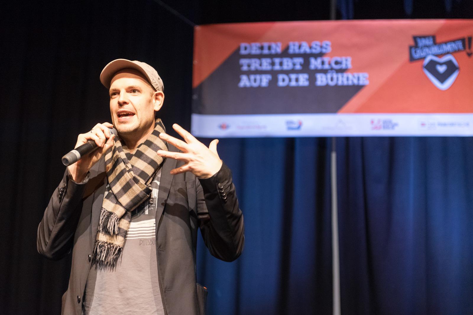 """Ein Mann steht auf einer Bühne. Er hat ein Mikrophone in der Hand und spricht. Im Hintergrund hängt ein Plakat auf dem steht: """"Dein Hass treibt mich auf die Bühne."""""""