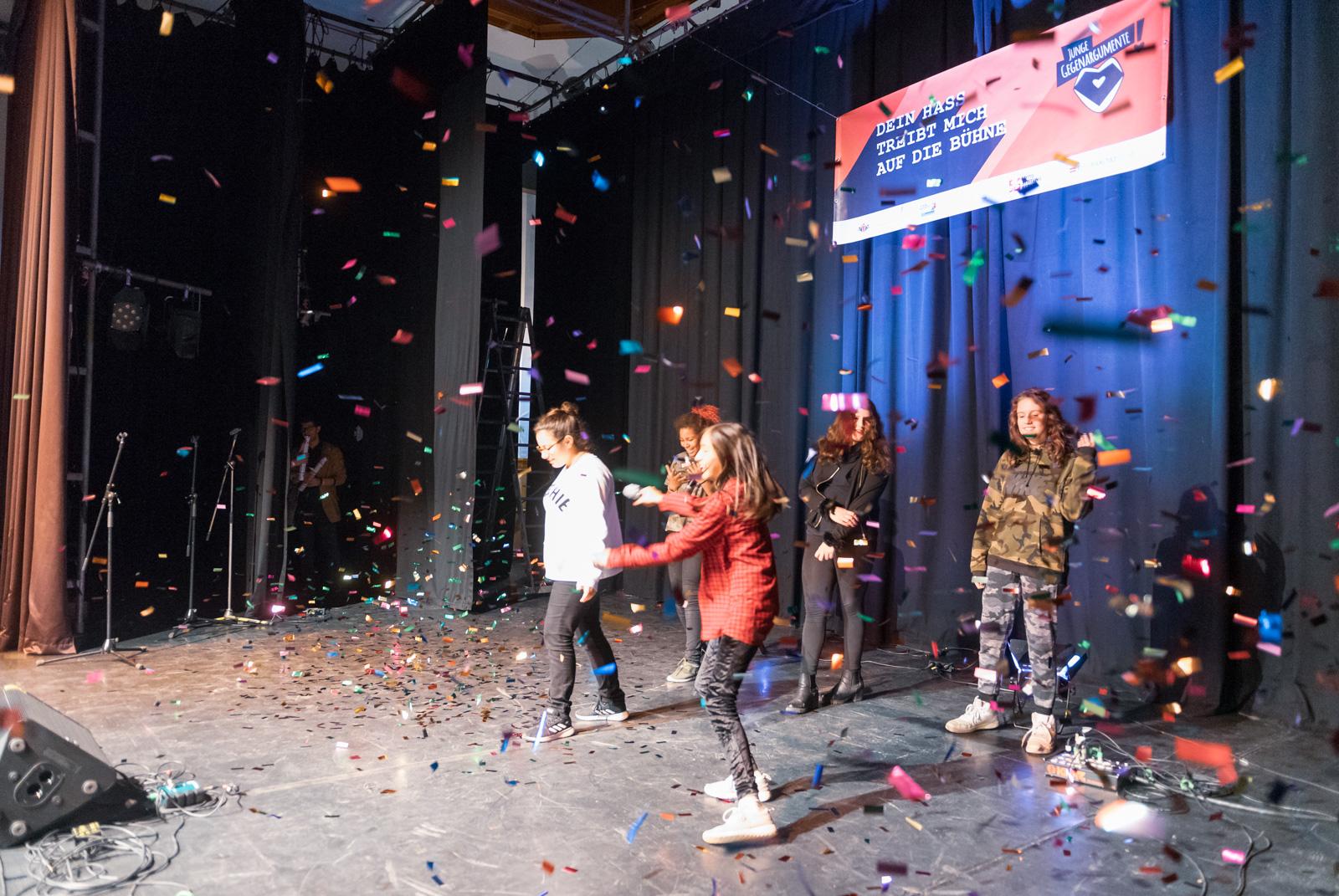 """Fünf junge Menschen stehen auf einer Bühne. Von oben regnet es Konfetti. Im Hintergrund hängt ein Plakat auf dem steht: """"Der Hass treibt mich auf die Bühne."""""""