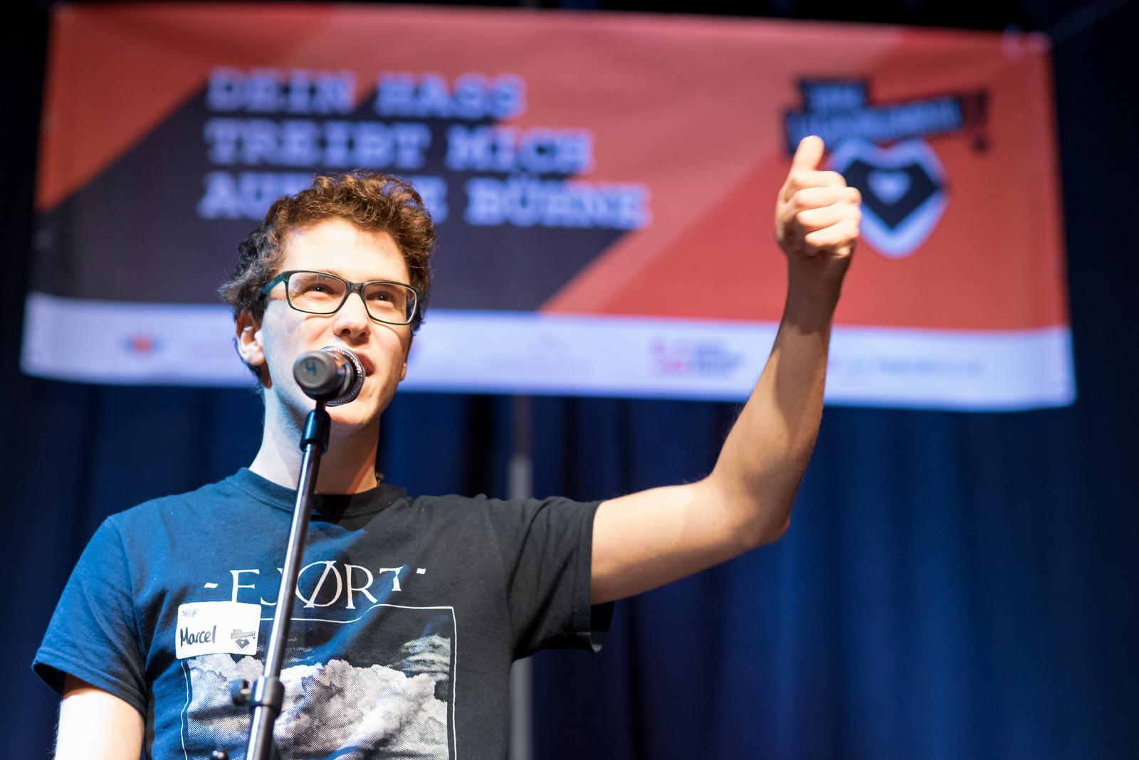 Ein junger Mann steht auf einer Bühne hinter einem Mikrophone. Er spricht in der Mikrophone und hebt einen Arm mit Daumen nach oben.