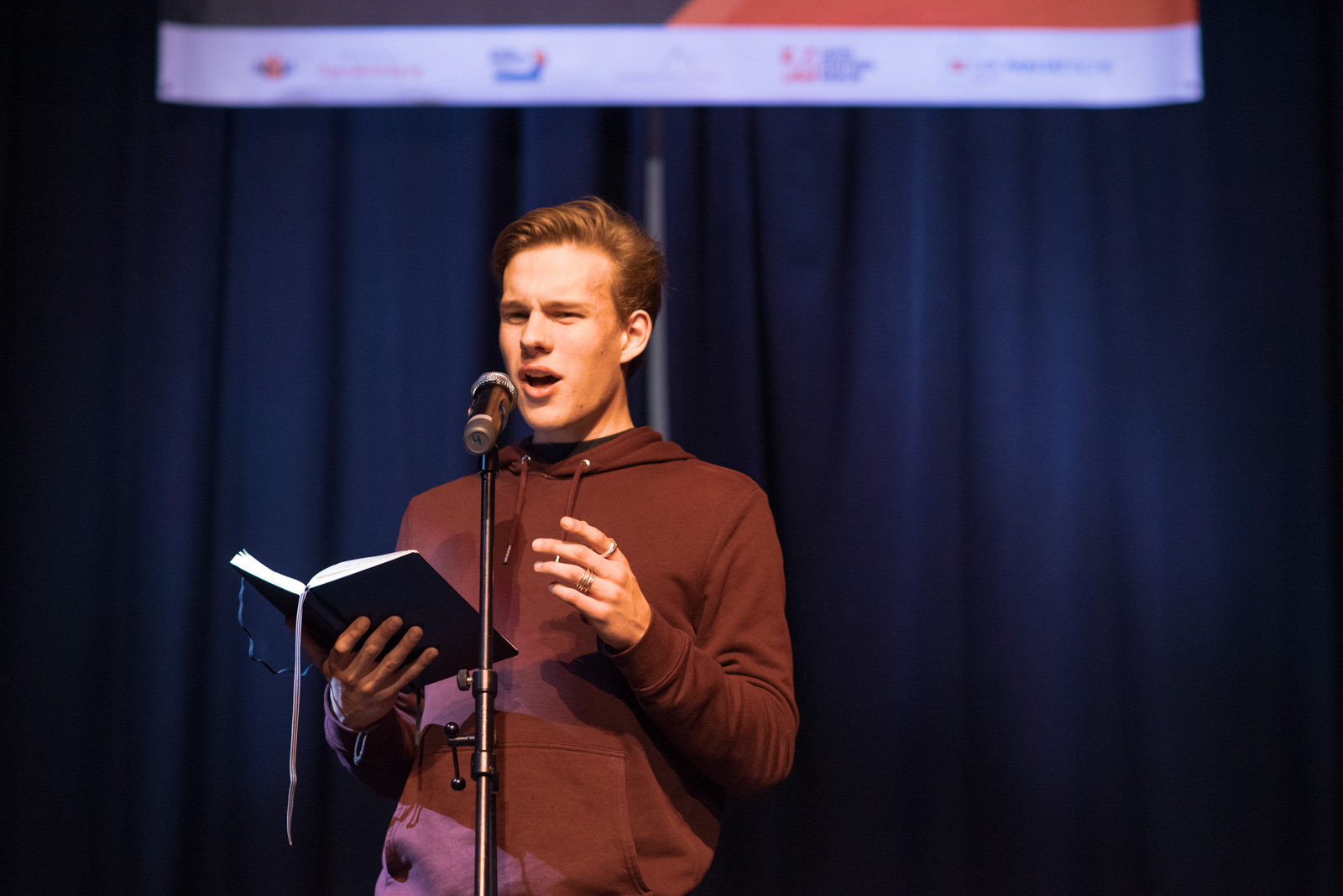 Ein junger Mann steht auf einer Bühne hinter einem Mikrophone. Er hält ein Notizbuch in der Hand und spricht.