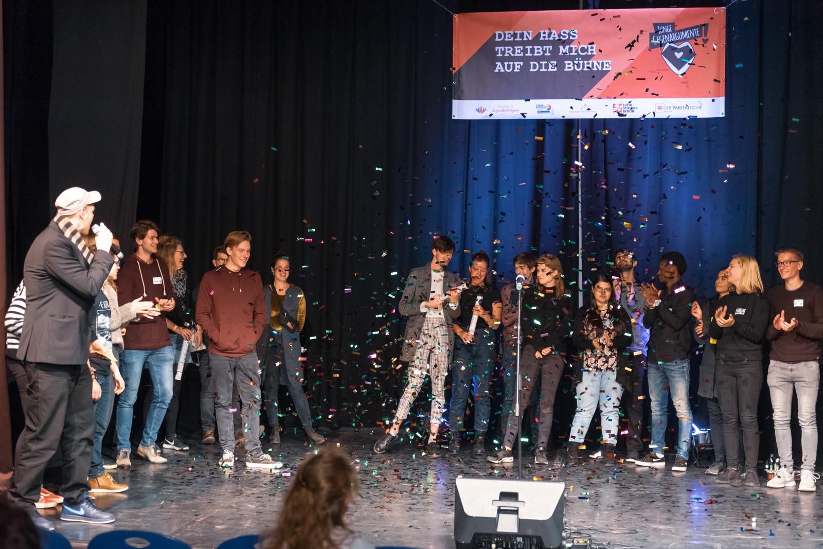 """Eine Gruppe junger Menschen steht auf einer Bühne. Sie klatschen und lachen. Es regnet Konfetti. Links steht ein Mann und spricht in ein Mikrophon. Im Hintergrund hängt ein Plakat auf dem steht: """"Dein Hass treibt mich auf die Bühne""""."""