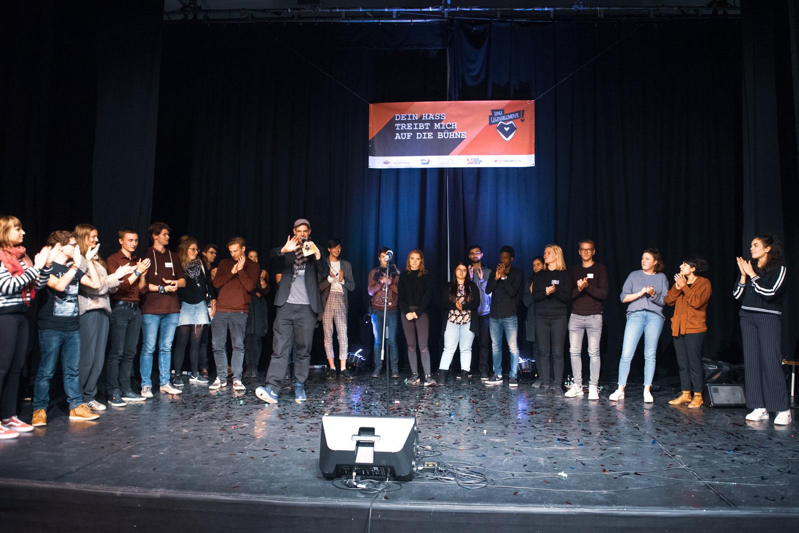 """Eine Gruppe junger Menschen steht auf einer Bühne und klatscht. Ein Mann spricht in ein Mikrophon. Im Hintergrund hängt ein Plakat auf dem steht: """"Dein Hass treibt mich auf die Bühne"""". Auf der Bühne liegt Konfetti."""