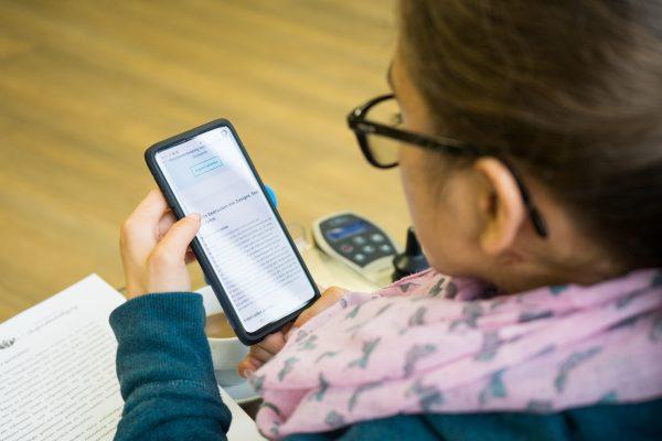 Das Bild zeigt eine Frau, die etwas auf ihrem Handy liest. © Servicestelle Jugendbeteiligung e.V., 2019