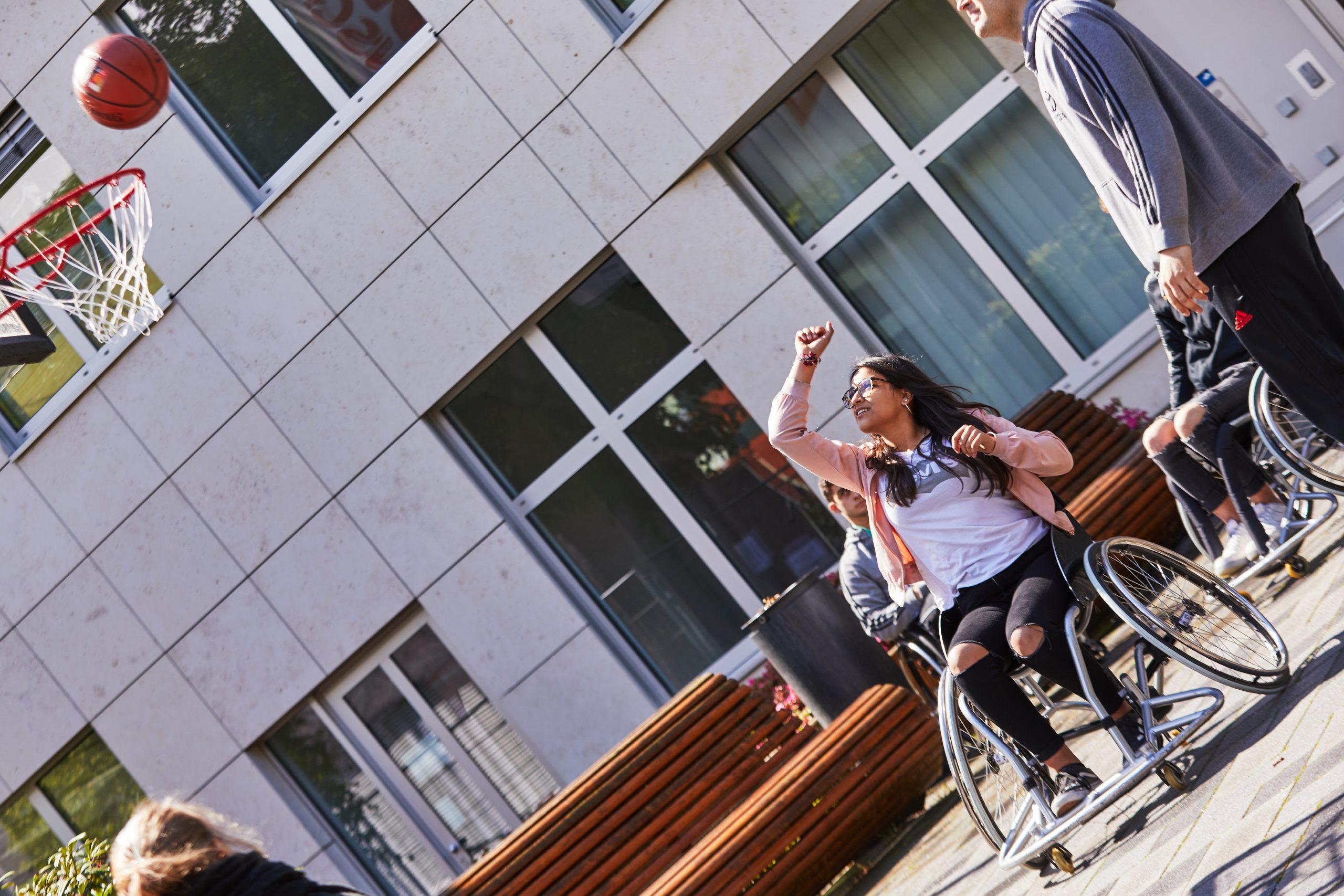 Eine junge Frau sitzt in einem Rollstuhl und wirft mit einem Basketball auf einen Basketballkorb. Neben ihr steht ein junger Mann.
