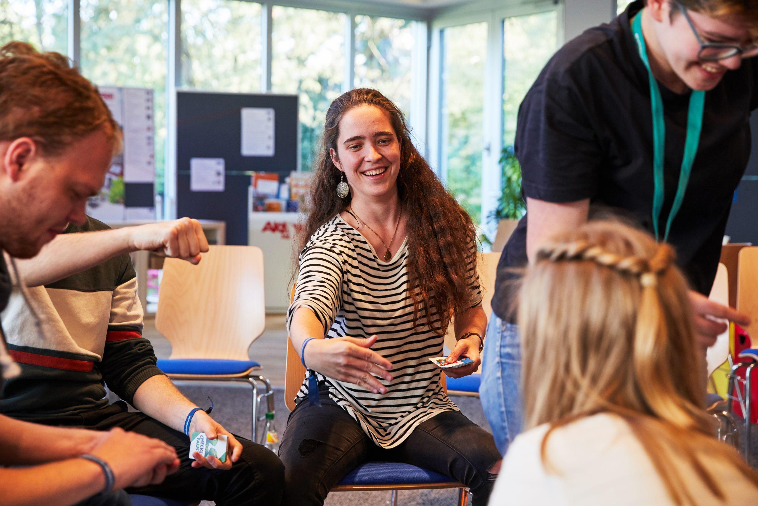 Junge Menschen sitzen in einem Raum in einem Stuhlkreis und spielen Karten.