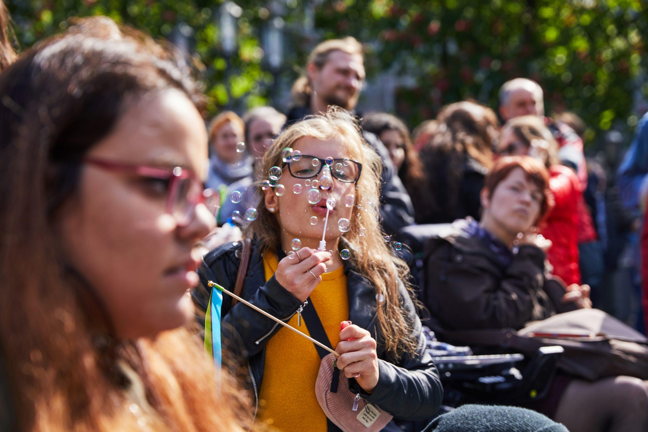Eine junge Frau pustet Seifenblasen. Um die junge Frau herum sind weitere Personen zu sehen.