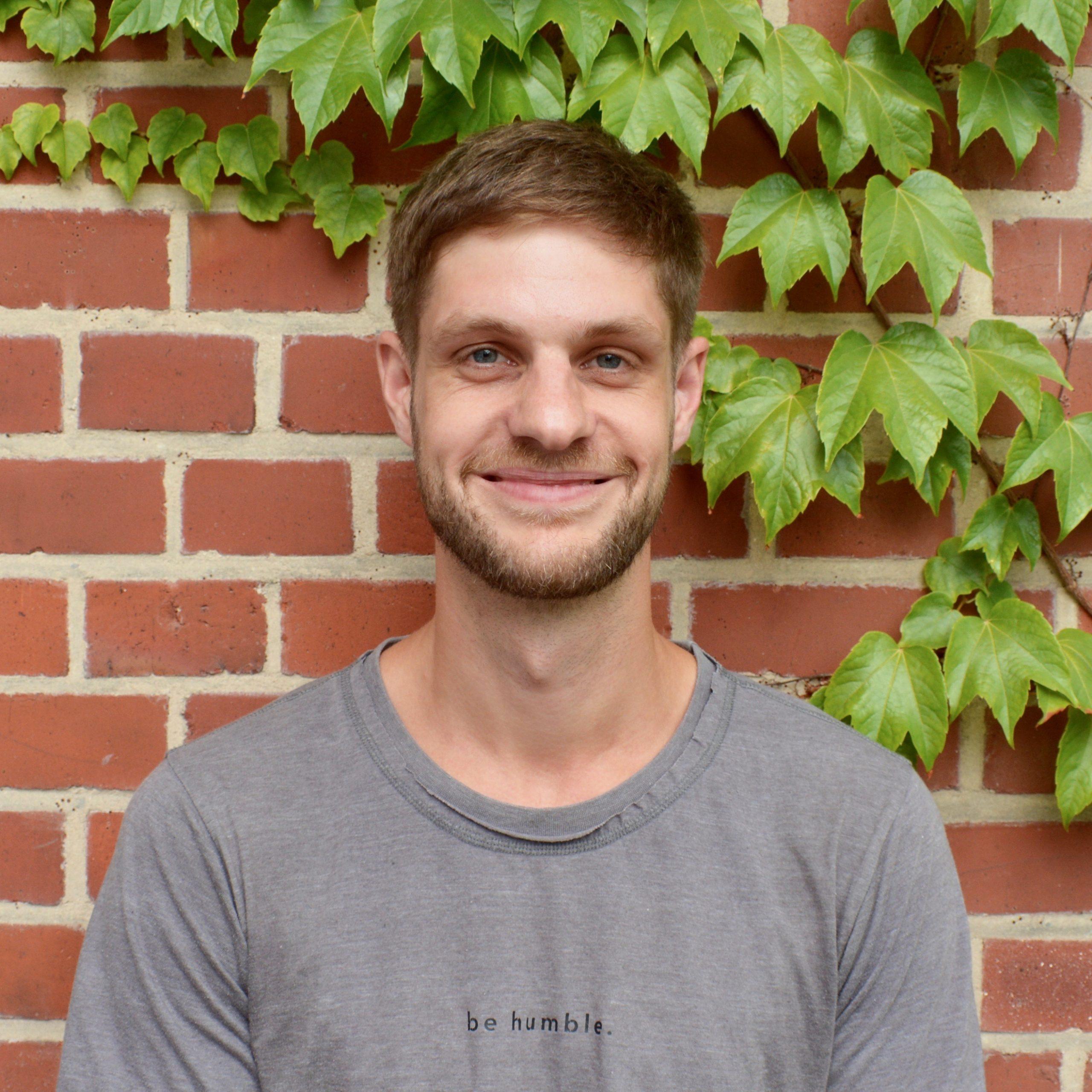 Das Bild zeigt Johann von der Servicestelle Jugendbeteiligung. Er steht vor einer mit Efeu bewachsenen Backsteinwand und lacht in die Kamera. © Servicestelle Jugendbeteiligung e.V., 2020