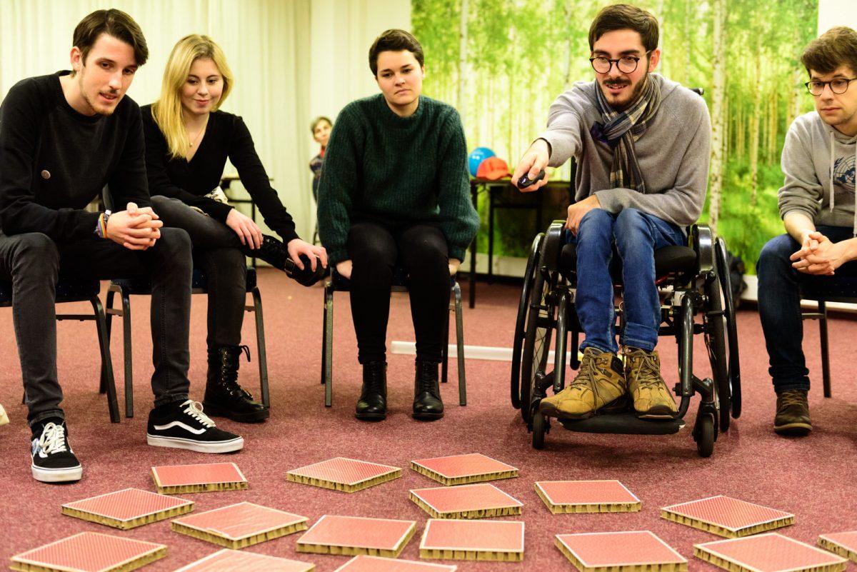 Fünf junge Menschen sitzen in einer Reihe nebeneinander. Auf dem Boden liegen verdeckte Karten verteilt. Die zweite Person von rechts ist ein junger Mann. Er sitzt im Rollstuhl und zeigt mit einem Laserpointer auf eine der Karten, die auf dem Boden liegen.