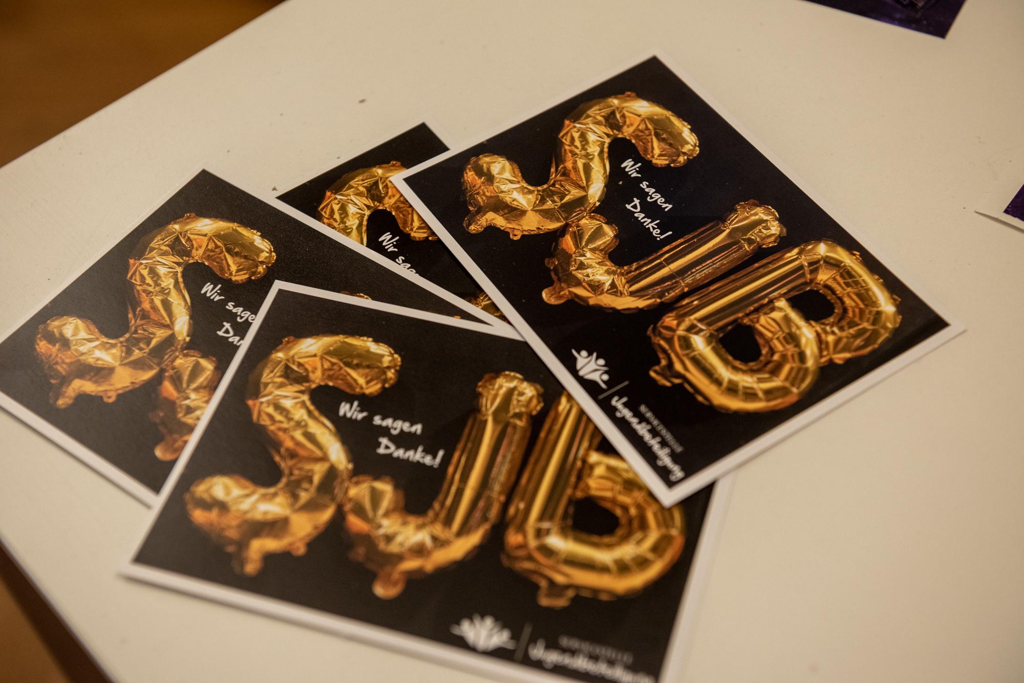 """Auf einem Tisch liegen Postkarten. Auf den Postkarten ist sind goldene Folienballons zu sehen. Die Ballons bilden das Wort SJB. Außerdem steht """"Wir sagen Danke!"""" auf den Karten und das Logo der Servicestelle Jugendbeteiligung ist zu sehen."""