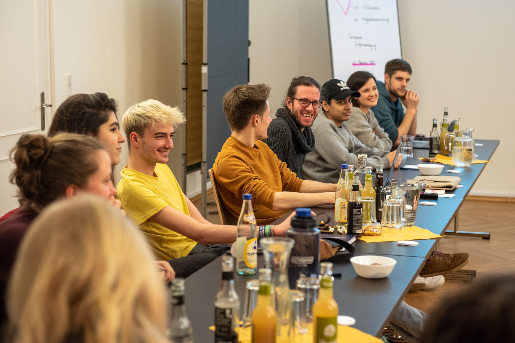 Mehrer junge Menschen sitzen an einem langen Tisch. Auf dem Tisch stehen Getränke.