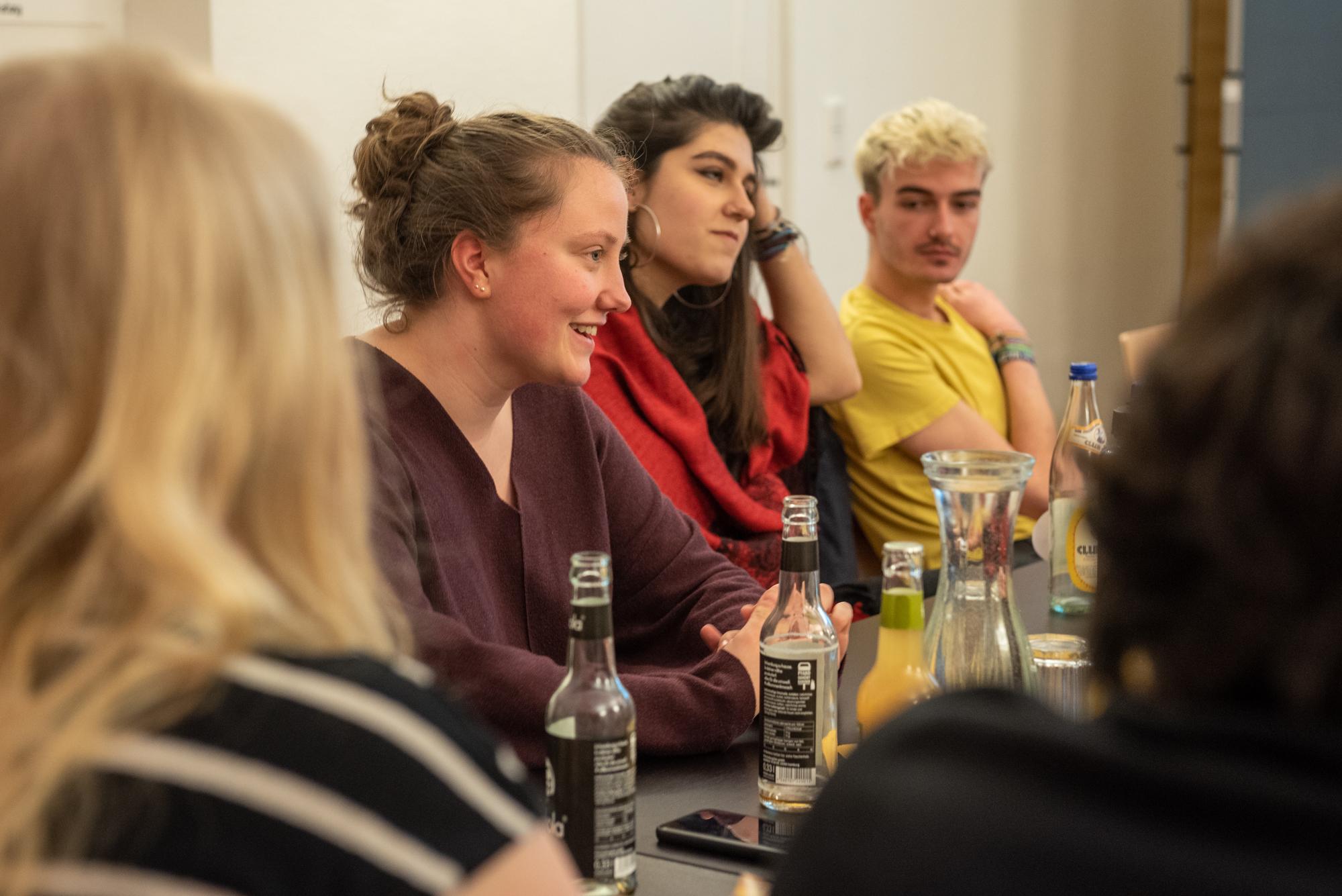 Mehrere Personen sitzen an einem Tisch und schauen in den Raum. Vor den Personen stehen Getränke.