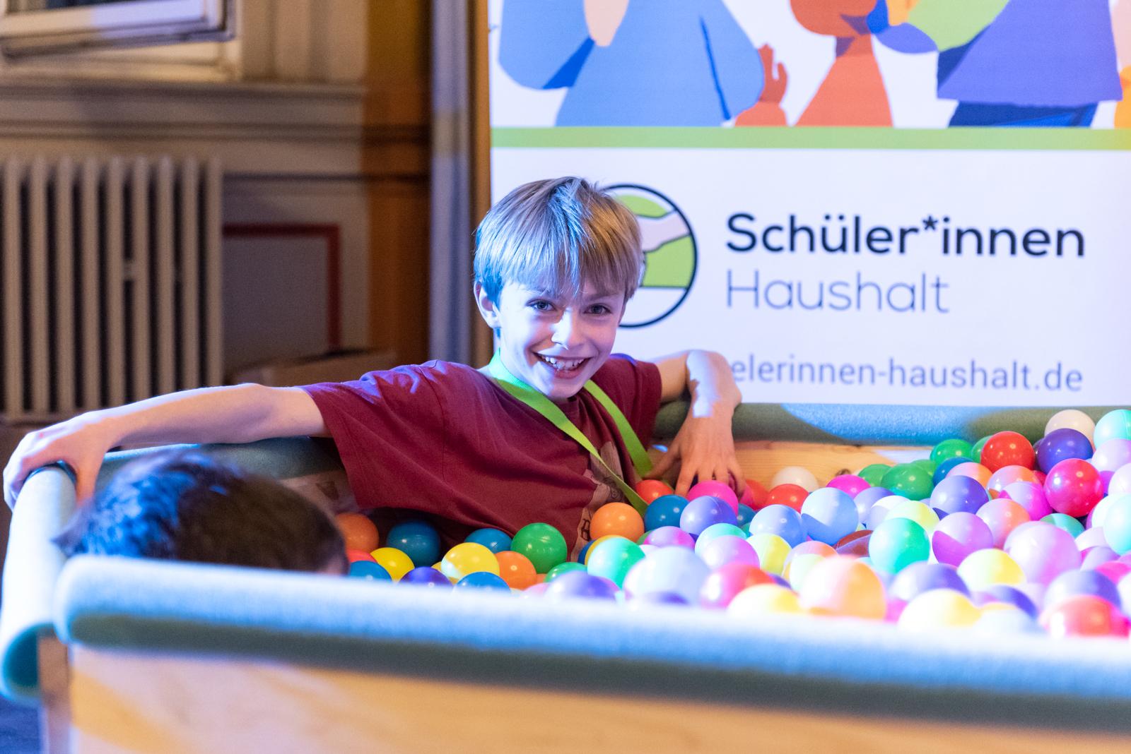 Ein Junge sitz in einem Bällebad. Der Junge lächelt in die Kamera. Im Hintergrund ist ein Plakat des Schüler*innen Haushalts zu sehen.