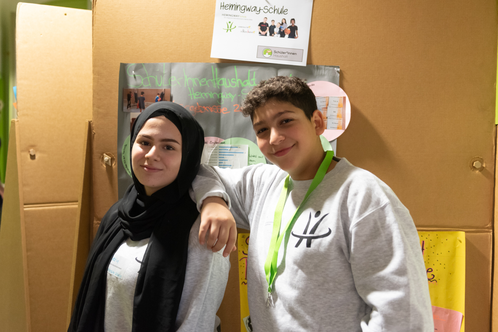 Zwei junge Menschen stehen vor einer Stellwand. An der Stellwand hängt ein Plakat. Die beiden jungen Menschen lächeln in die Kamera.