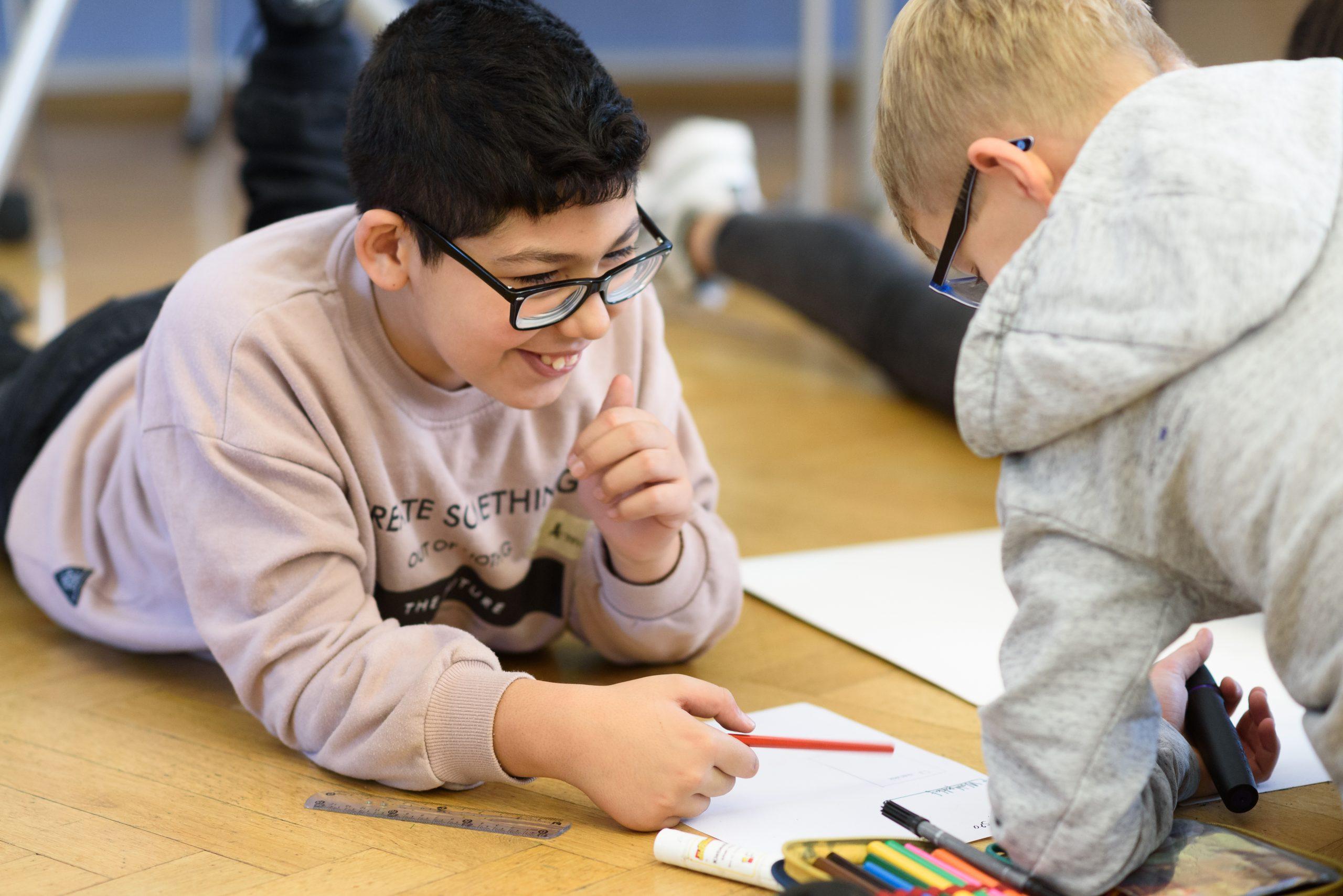 Auf dem Bild sieht man zwei Personen auf dem Boden liegen und mit Buntstiften auf einem Blatt malen. Die eine Person lächelt. © Servicestelle Jugendbeteiligung e. V. 2019