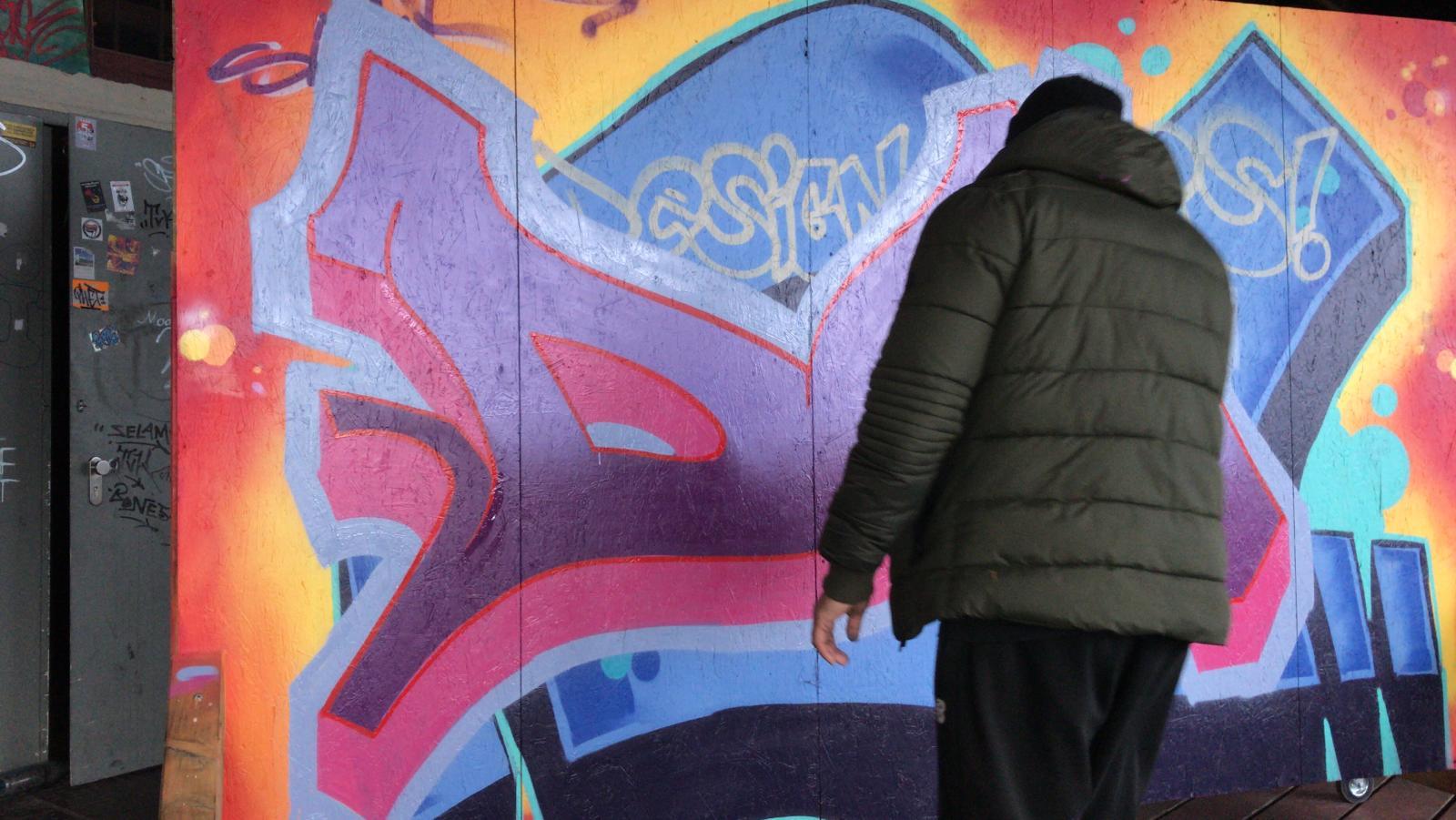 Eine Person steht vor einer Wand. Auf der Wand ist ein buntes Graffiti gesprüht.