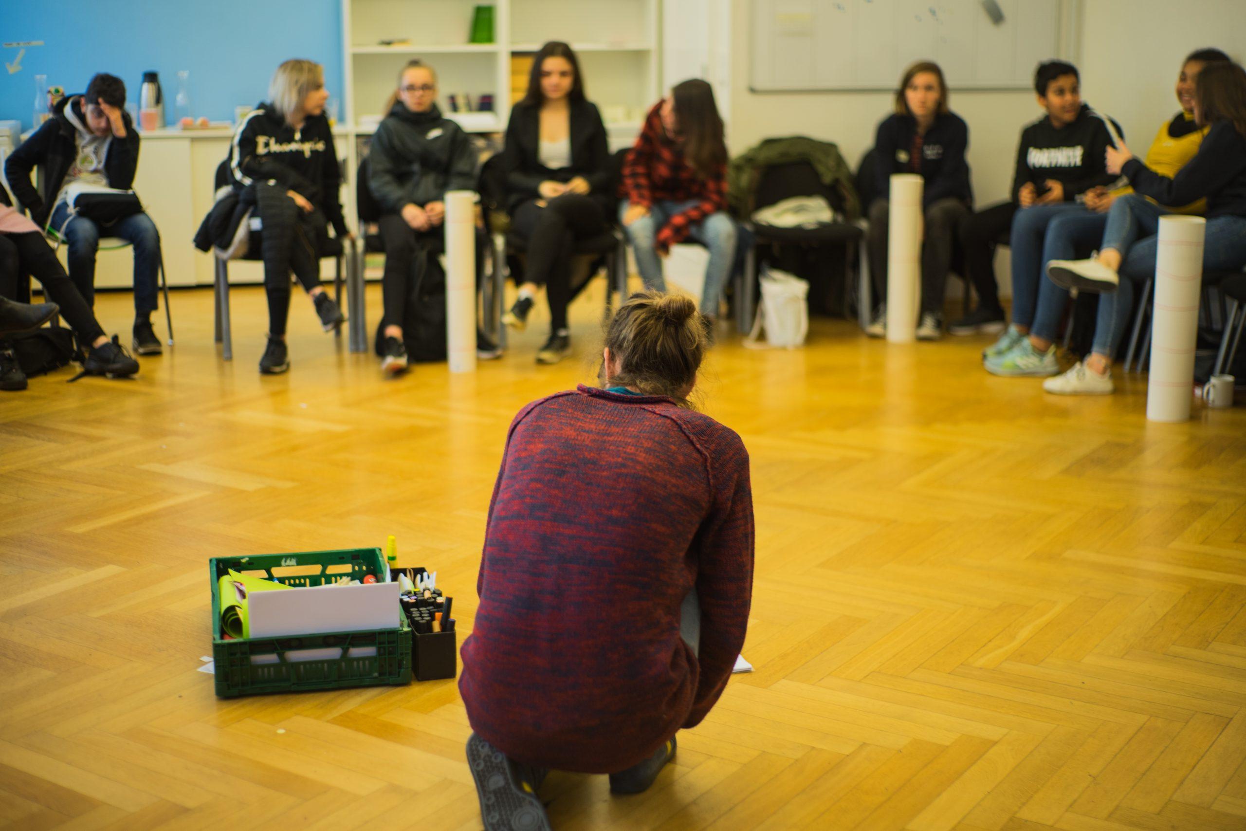Auf dem Bild sieht man verschiedene Menschen, die in einem Stuhklreis sitzen. In der Mitte kniet sich eine Person, um Moderationsmaterial für den nächsten inhaltlichen Block aufzuheben. © Servicestelle Jugendbeteiligung e.V., 2019
