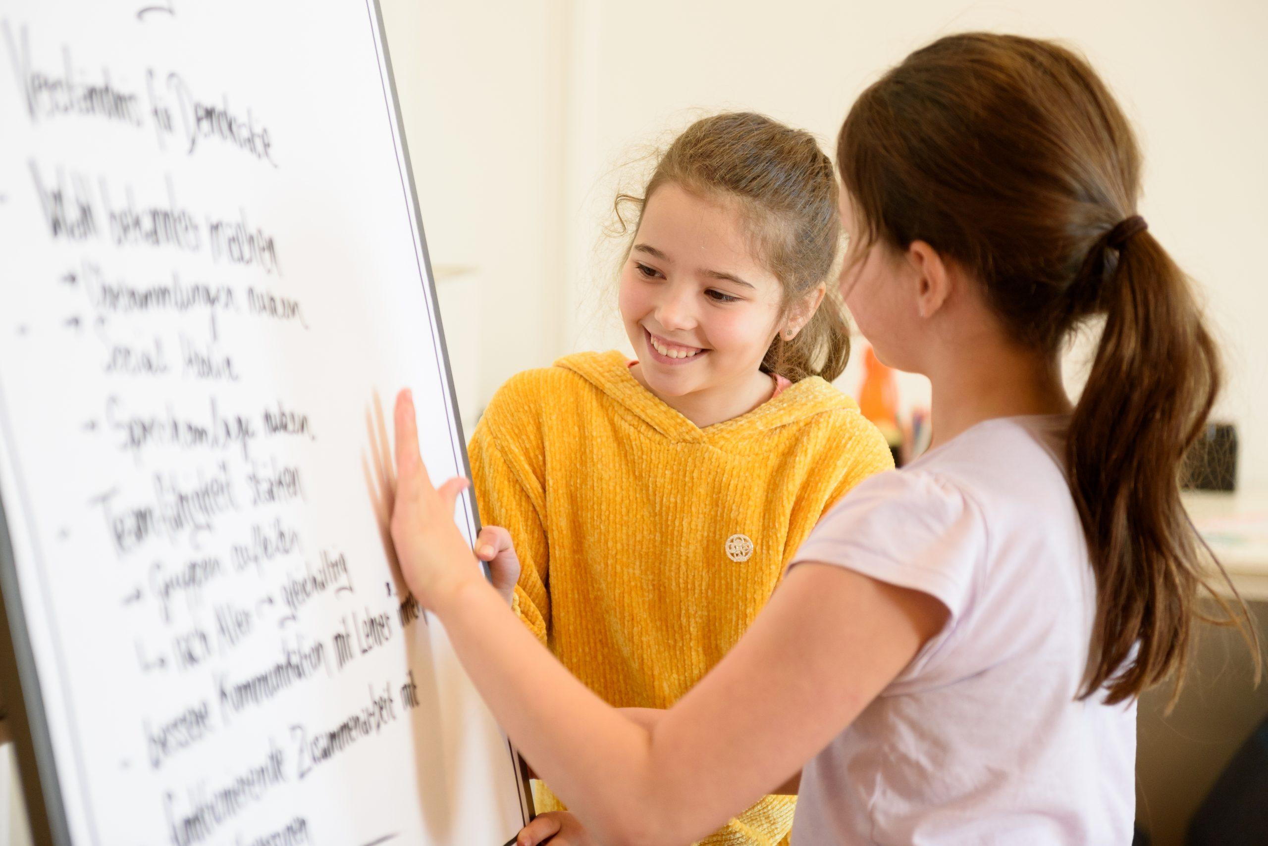 Zwei Mädchen stehen vor einem Flipchart und schauen sich den geschrieben Text an.