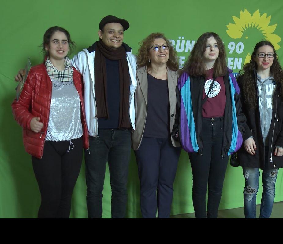 Fünf Personen stehen vor einer grünen Wand und lächeln in eine Kamera.