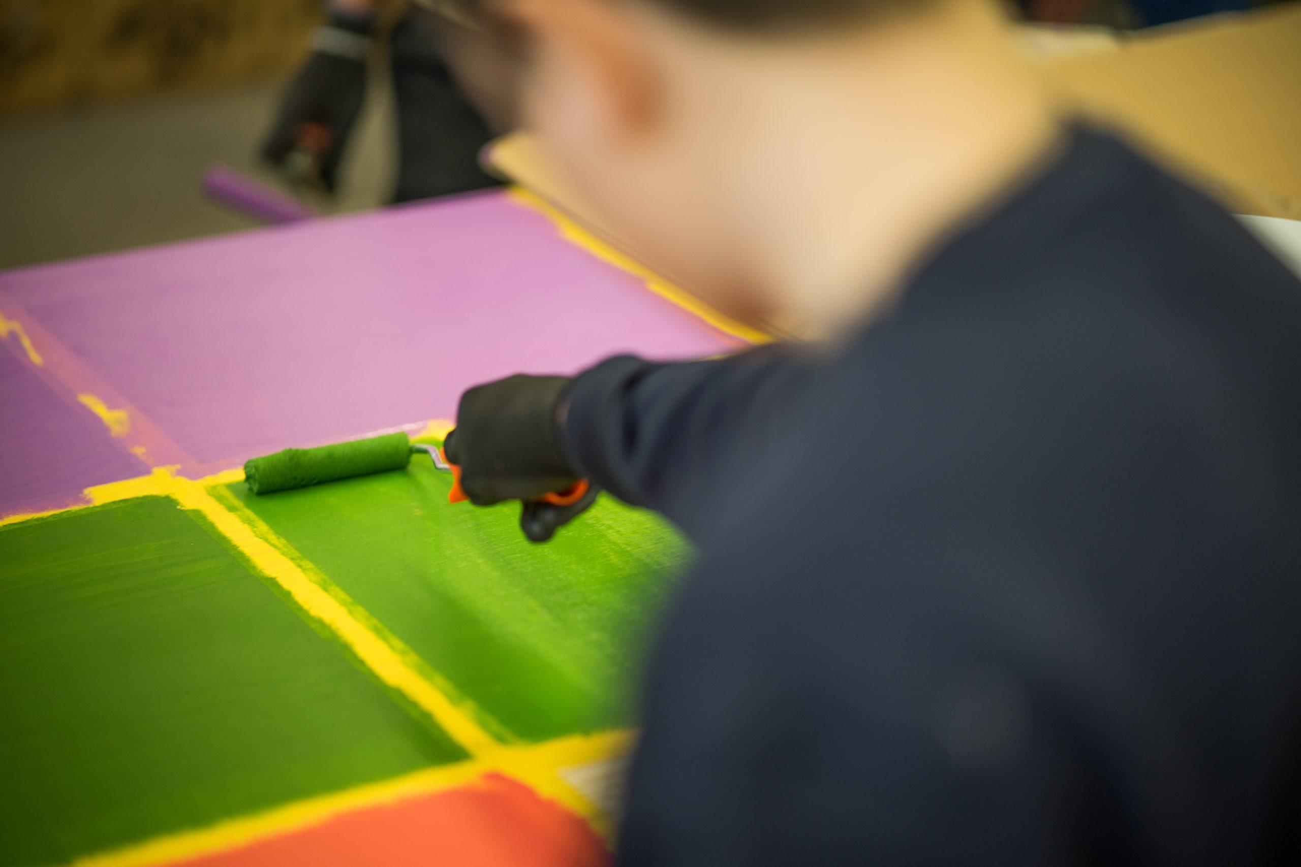 Eine Person streicht ein abgeklebtes Viereck auf einem Holzbrett grün.