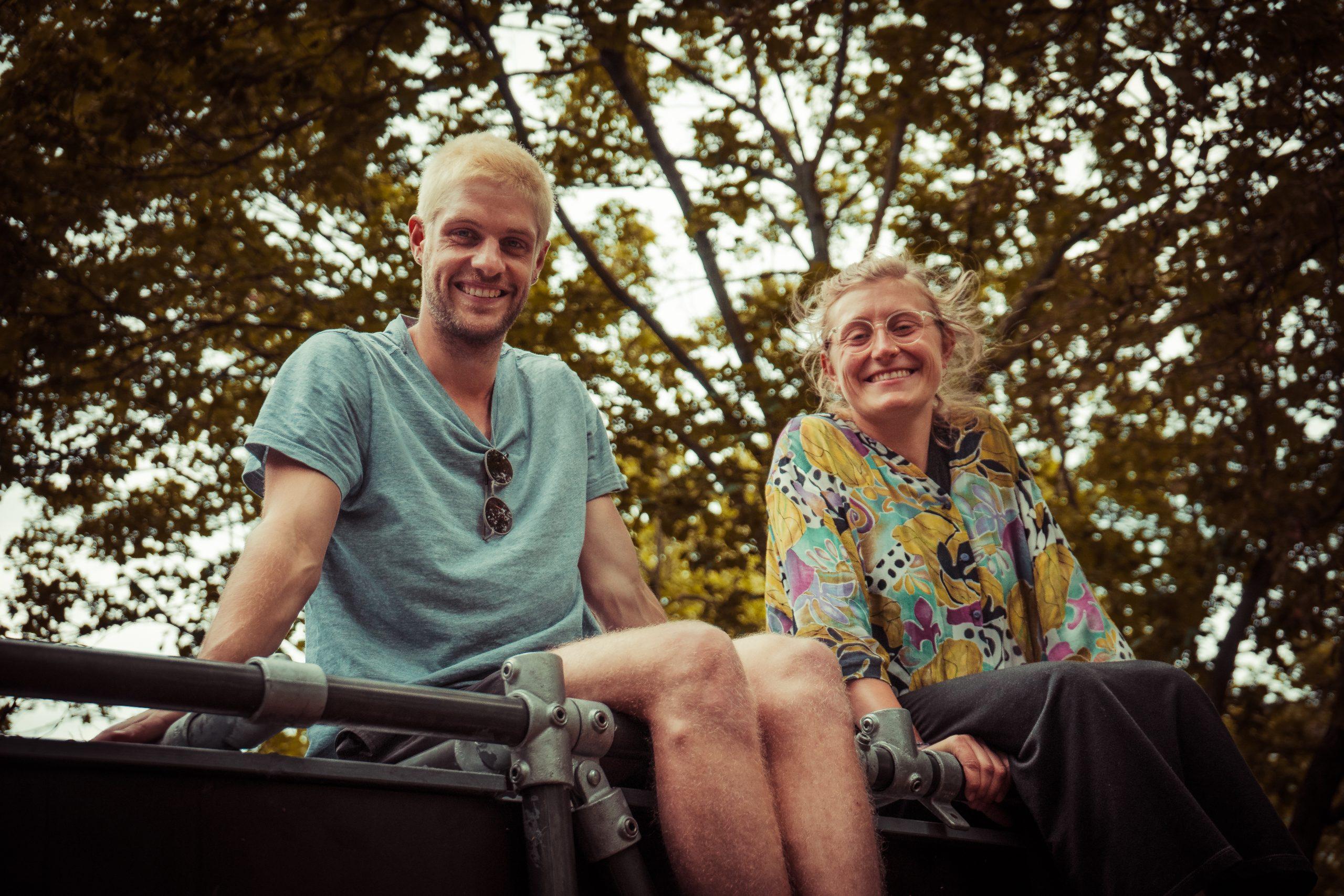 Ein junger Mann und eine junge Frau sitzen lachend auf einem Gerüst. Im Hintergrund sind Bäume zu sehen.