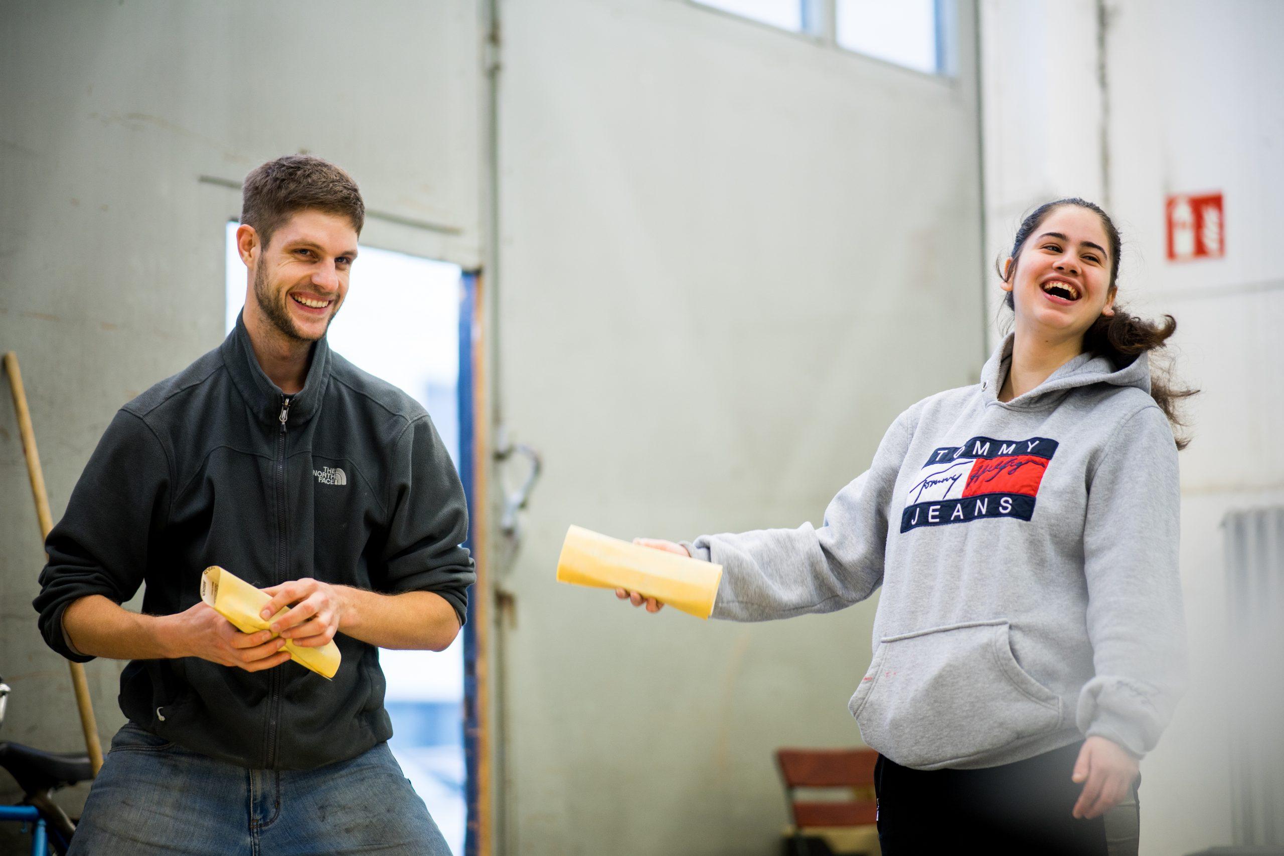 Ein junger Mann und eine junge Frau stehen lachend in einer Halle. Die beiden halten Schleifpapier in der Hand.