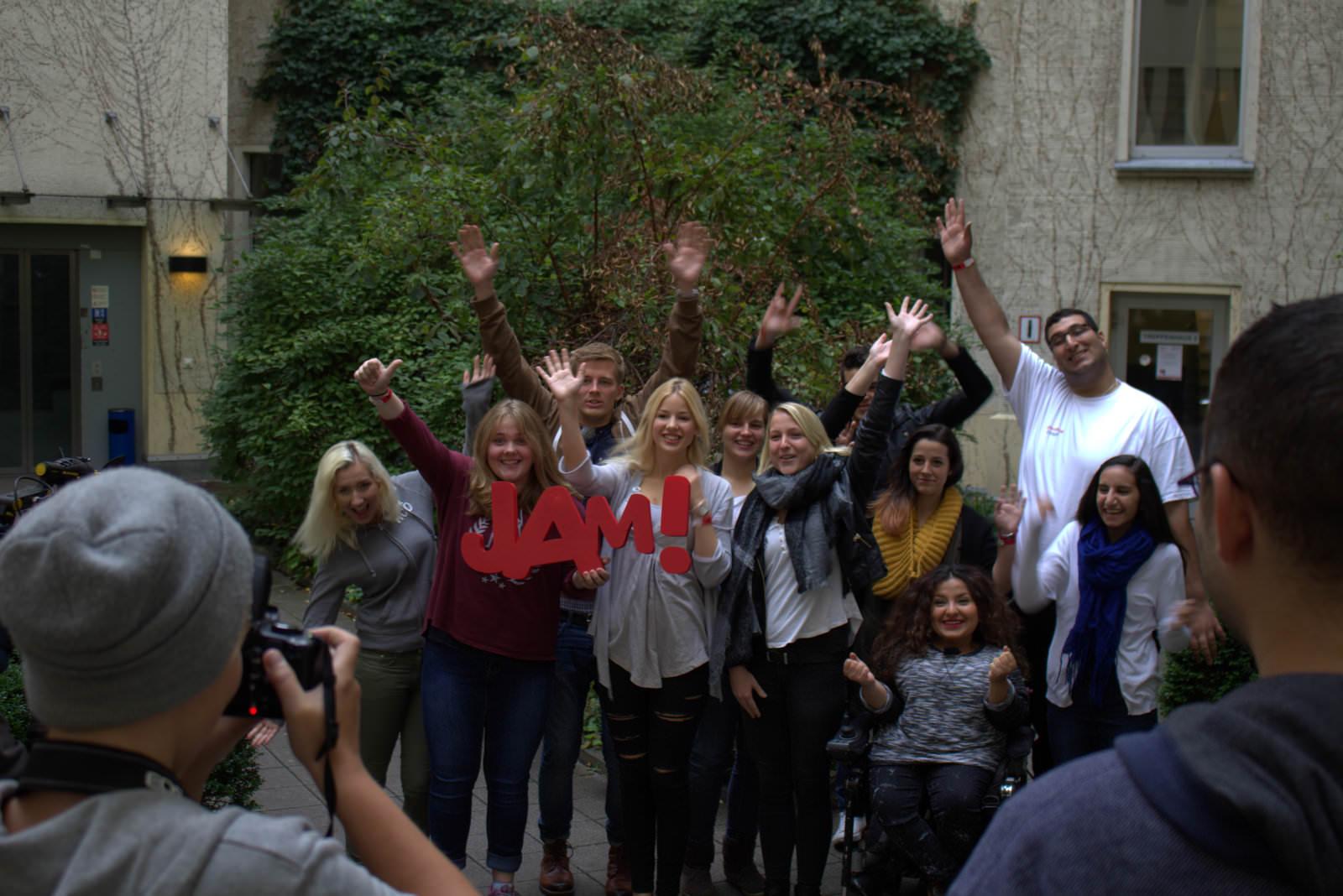 Eine Gruppe junger Menschen steht zusammen und steckt die Hände nach oben. Zwei junge Frauen im Vordergrund halten das JAM Logo.