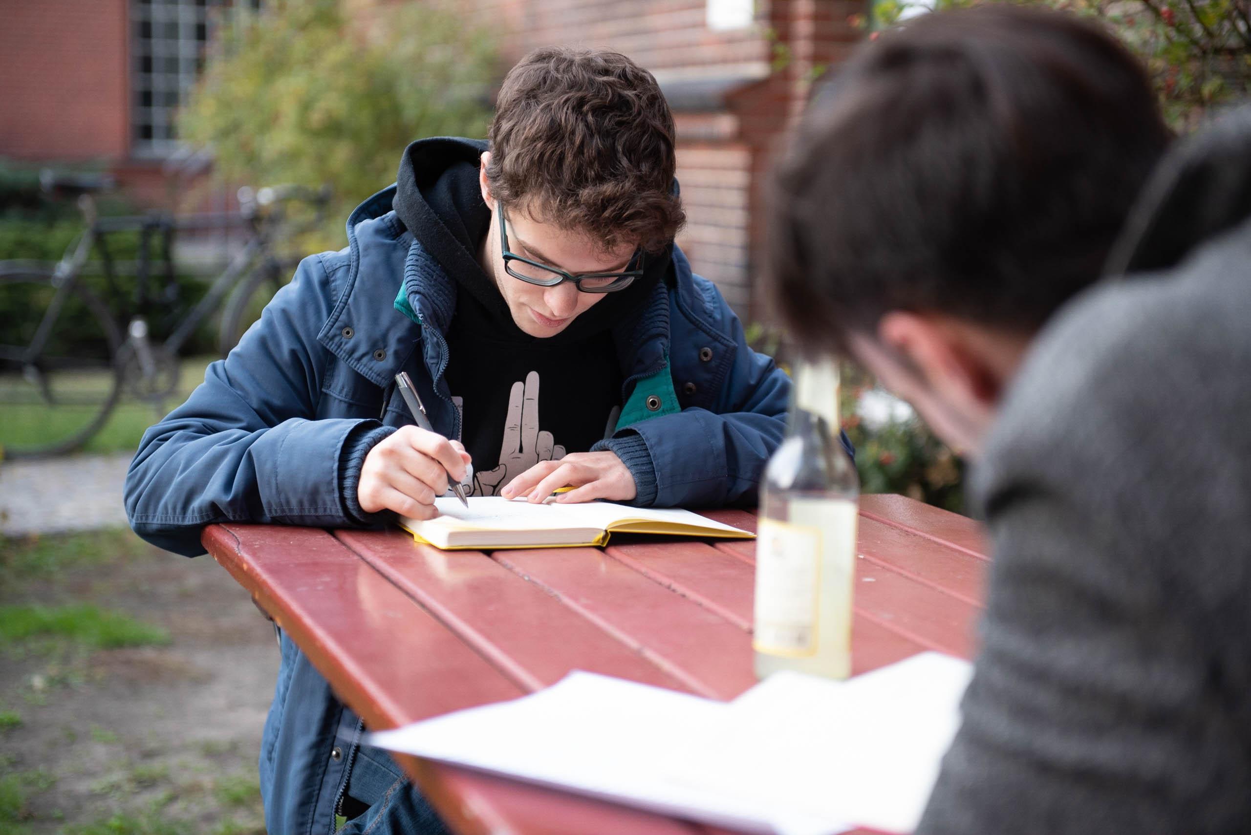 Auf dem Bild sieht man zwei Personen, die an einem Tisch sitzen und etwas aufschreiben. .© Servicestelle Jugendbeteiligung e.V., 2018