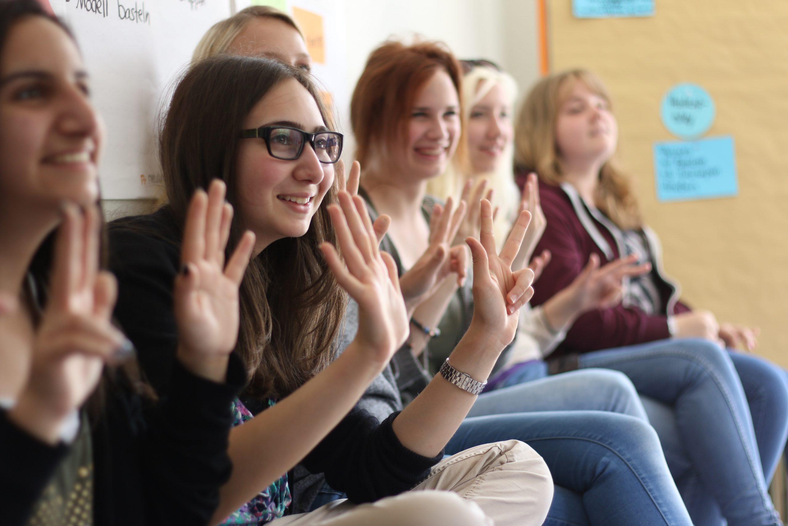 5 Menschen sitzen nebeneinander, lachen und heben die Hände um sich zu Wort zu melden.