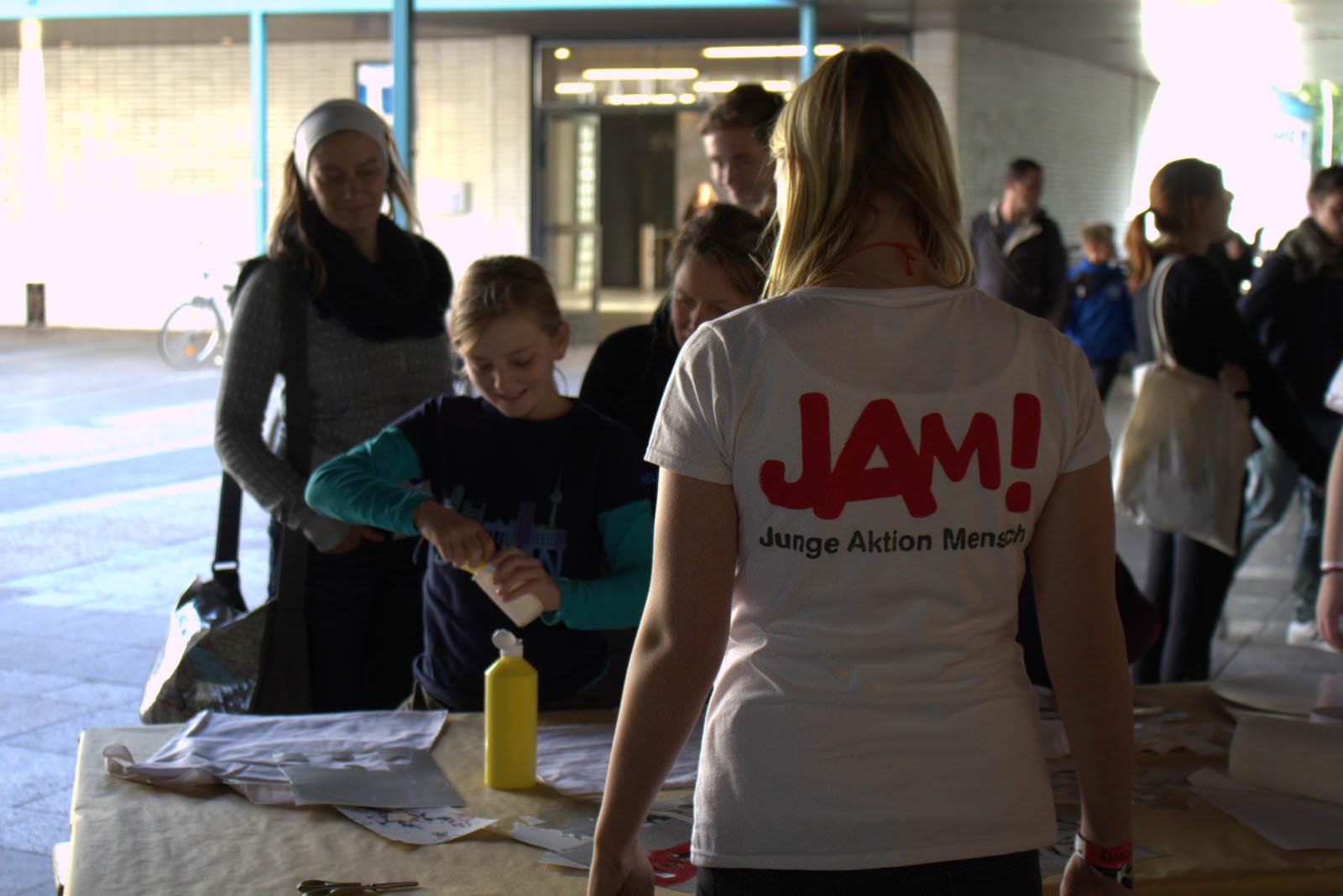 Eine Person steht mit dem Rücken zur Kamera. Sie trägt ein weißes Tshirt mit der Aufschrift JAM. Vor ihr steht ein Tisch und mehrere Menschen, die Taschen bemalen.