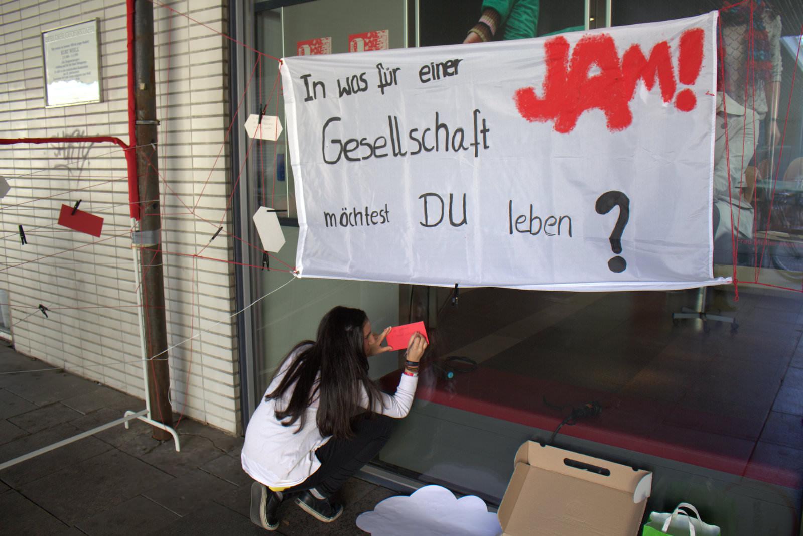 Ein Transparent hängt vor einer Glaswand. Darauf steht In was für einer Gesellschaft möchtest du leben? und das Logo von JAM. Darunter sitzt eine junge Frau und schreibt auf eine Karte.