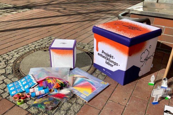 Bastelmaterialien liegen neben einer Stationsbox des Projektentwicklungslabors. © Servicestelle Jugendbeteiligung e. V., 2021