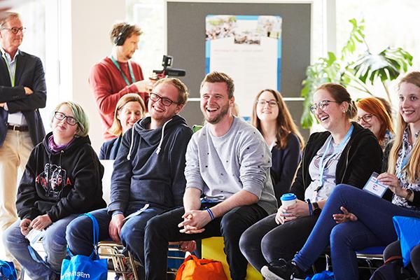 Das Bild zeigt mehrer junge Menschen, die im Plenum des Jugendaktionscamps 2019 sitzen und lachen © Anna Spindeldreiher, 2019