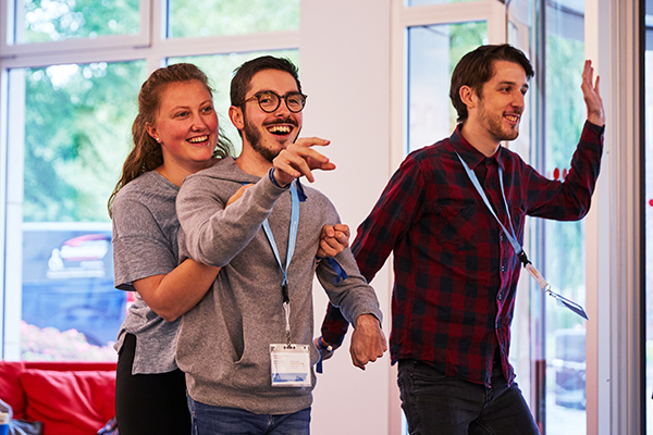 Das Bild zeigt drei Menschen, die zusammen einen Energizer spielen. Eine Person hebt die andere Person mit ihren Armen hoch, alle lachen. © Servicestelle Jugendbeteiligung e. V., 2019