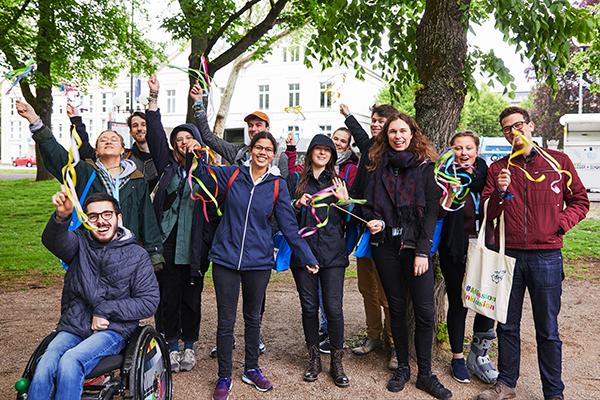 """Das Bild zeigt eine Gruppe junger Menschen, die lachend posieren und Stäbe mit bunten Bändern schwenken © Aktion Mensch e. V. / Servicestelle Jugendbeteiligung e. V./Anna Spindelndreier, 2019"""""""