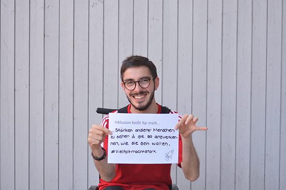 """Ein junger Mann im Rollstuhl hält ein weißes Blatt vor sich in den Händen. Die Aufschrift lautet: """"Inklusion heißt für mich: Stärken anderer Menschen zu sehen und sie so anzuerkennen wie sie sein wollen"""". © Servicestelle Jugendbeteiligung e. V., 2018"""