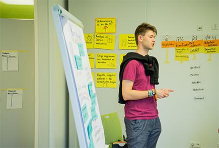 Das Bild zeigt einen jungen Mann, der vor einem Flipchart steht und etwas erklärt. Im Hintergrund sind viele Moderationskarten an die Wand gepinnt. © Servicestelle Jugendbeteiligung e.V., 2019