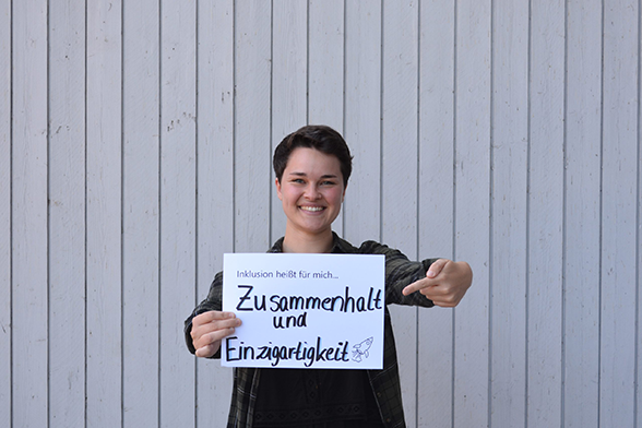 """Das Bild zeigt einen jungen Menschen, der vor einer weißen Wand steht. Sie hält ein Schild in der Hand, auf dem steht """"Inklusion heißt für mich, Zusammenhalt und Einzigartigkeit"""" © Servicestelle Jugendbeteiligung e.V., 2018"""